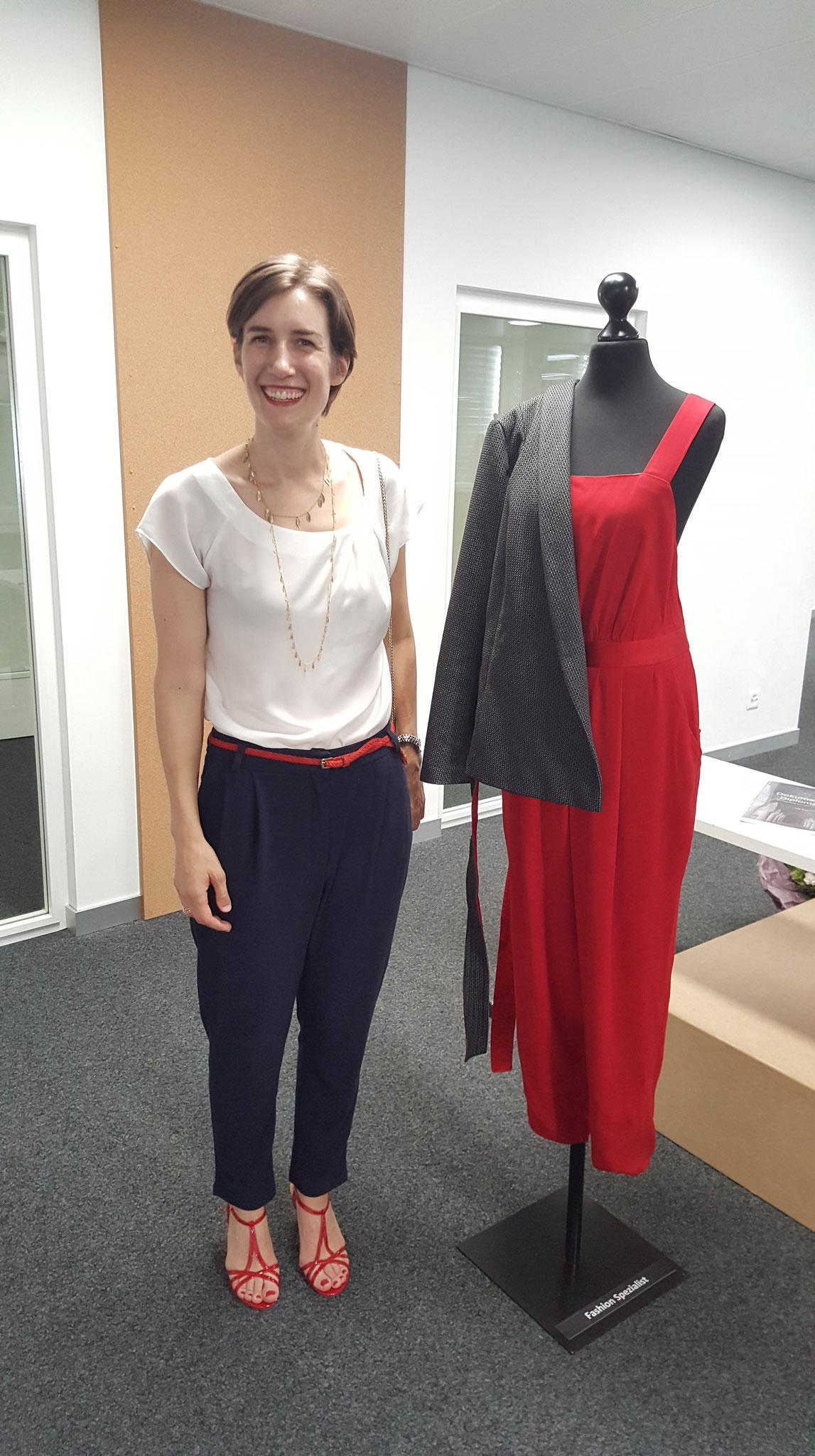 Joanna in einem Lieblingsoutfit, neben ihrer Abschlussarbeit von der STF.