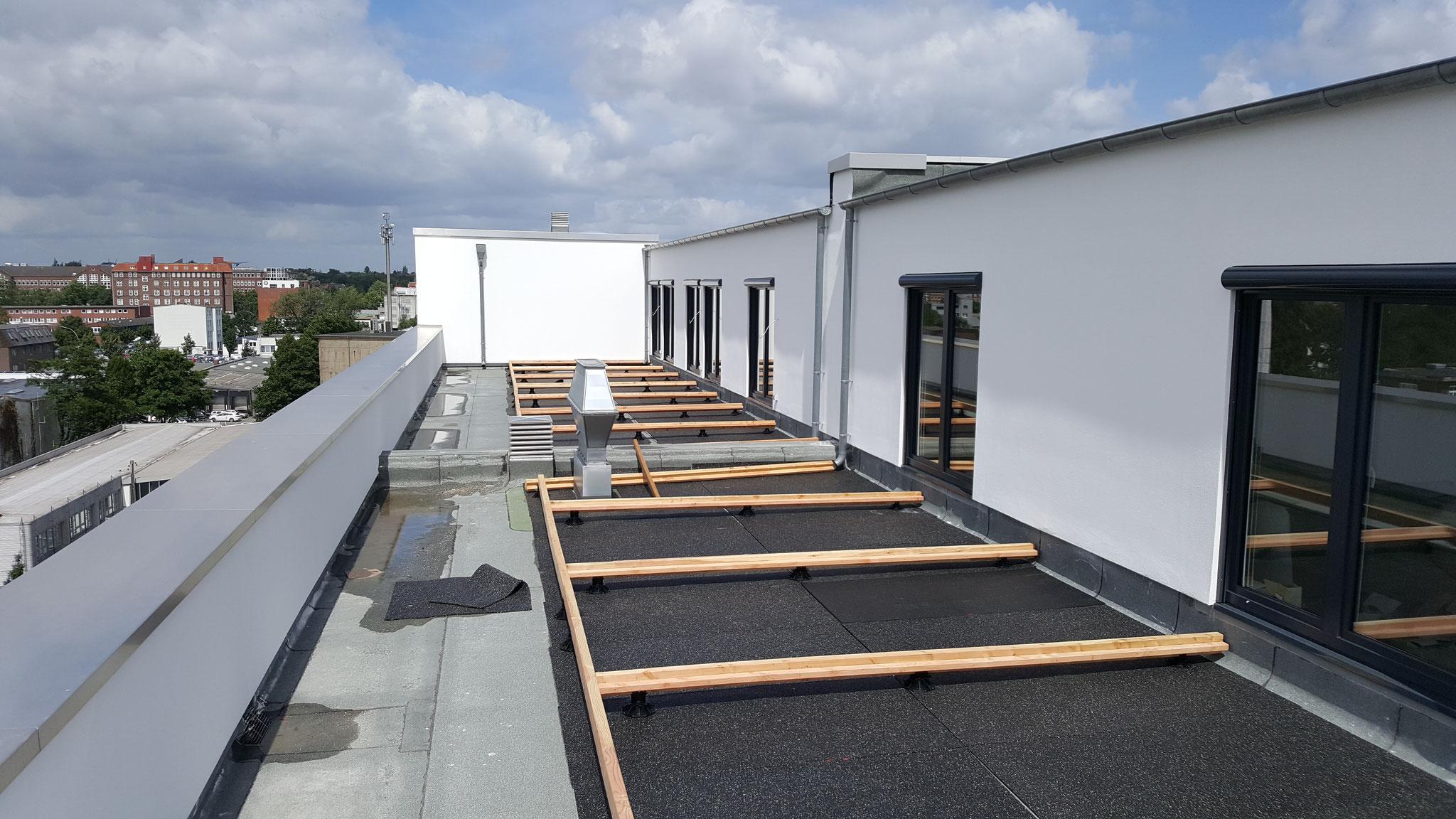 Vorbereiten der Unterkonstruktion für eine Dachterrasse. Die Konstruktion wurde auf verstellbare Terrassenfüße gestellt.