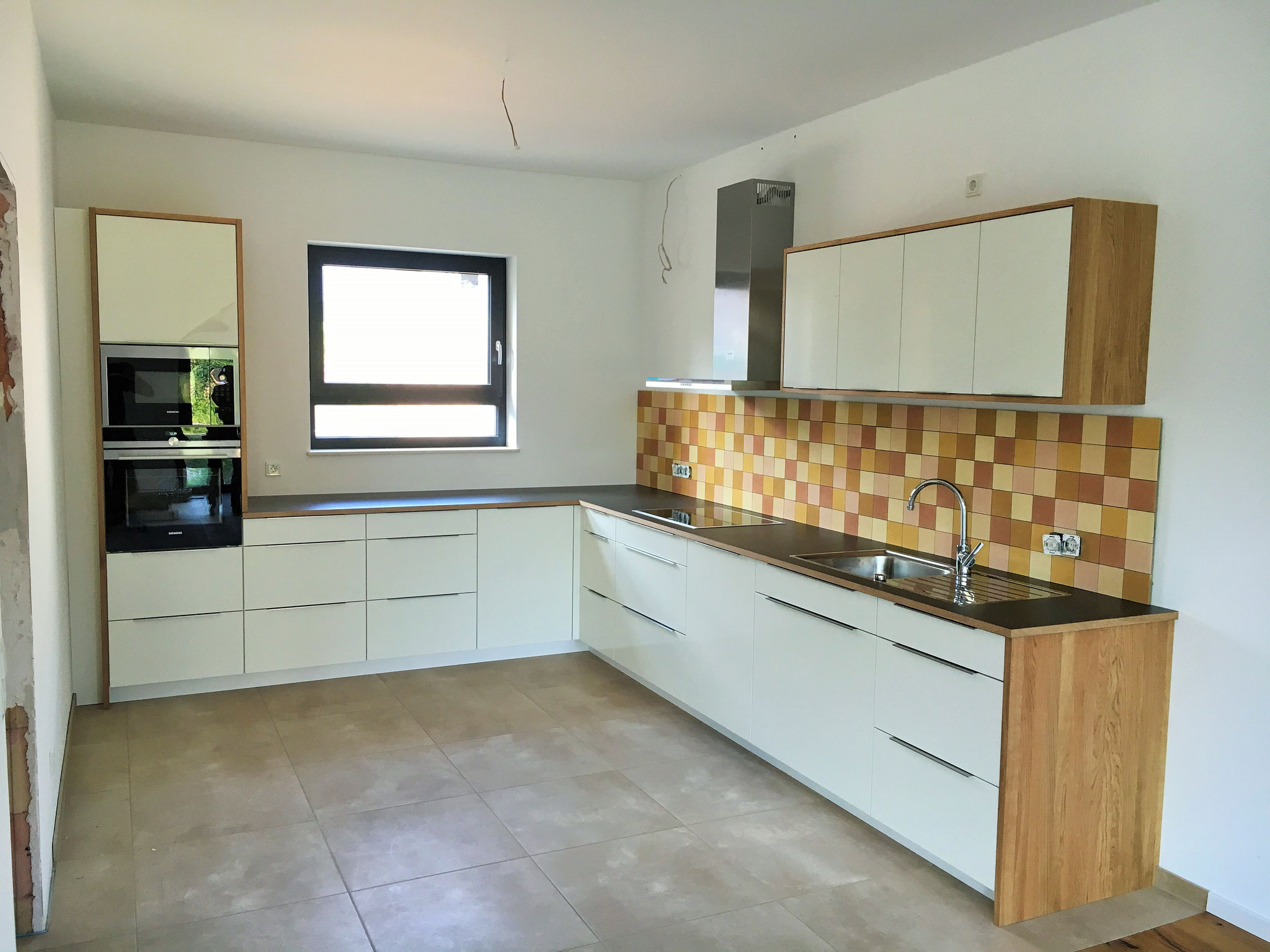 Offene Küche mit matten Küchenfronten und Eiche in Kombination