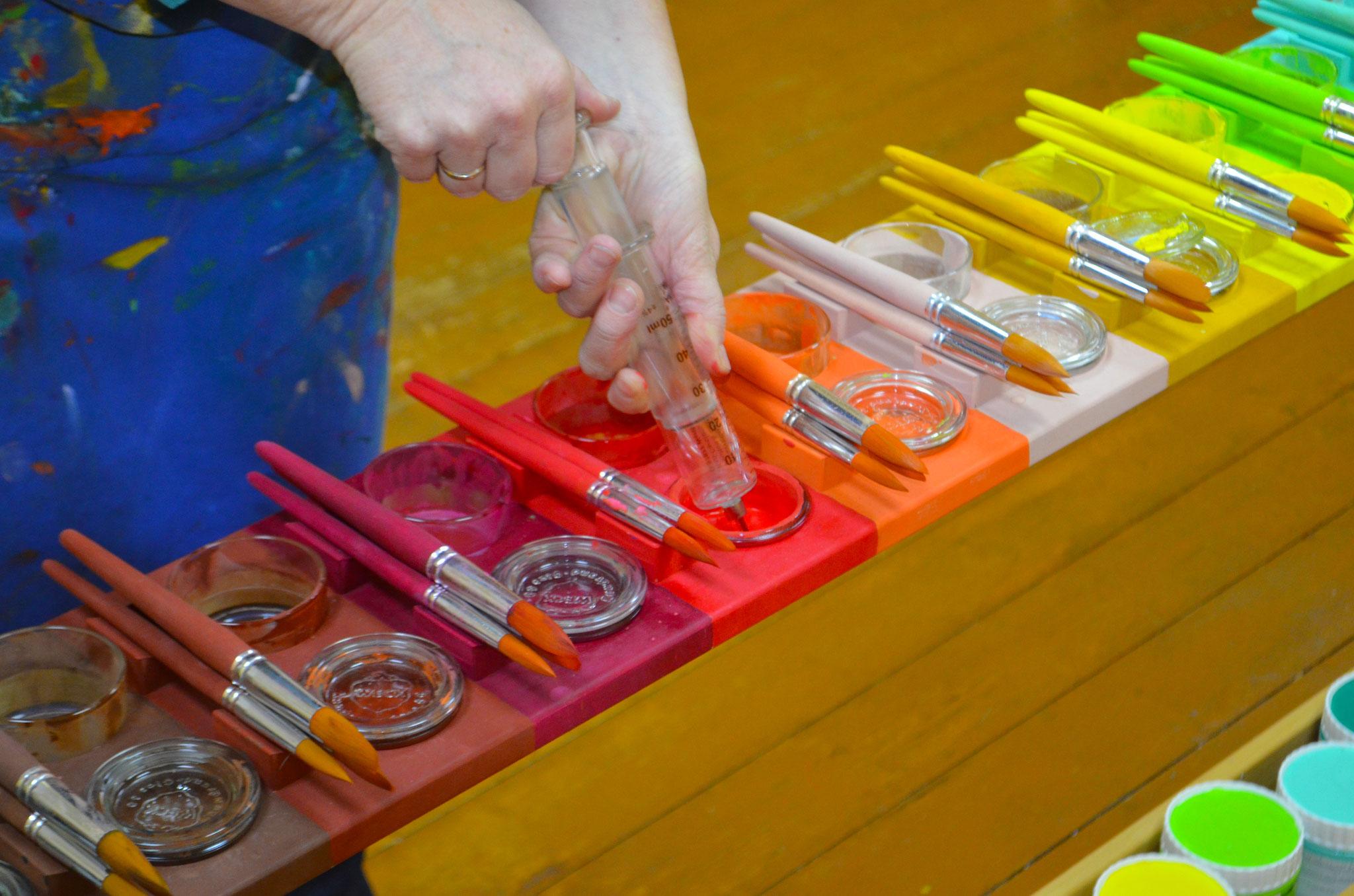 Wasser, welches die Farben zwischen den Malspielen befeuchtet, absaugen.