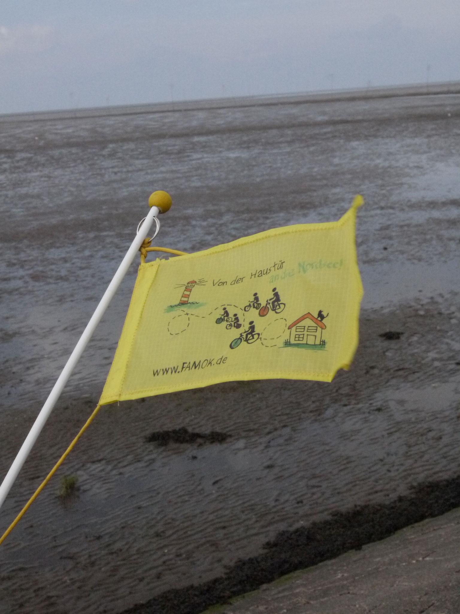 Unsere Tourflagge, im Hintergrund das verebbte Meer