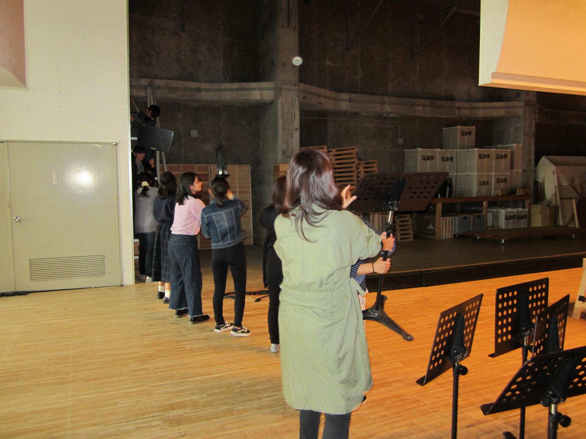 そして、いよいよ舞台設営へ。恒例の「譜面台」リレー。