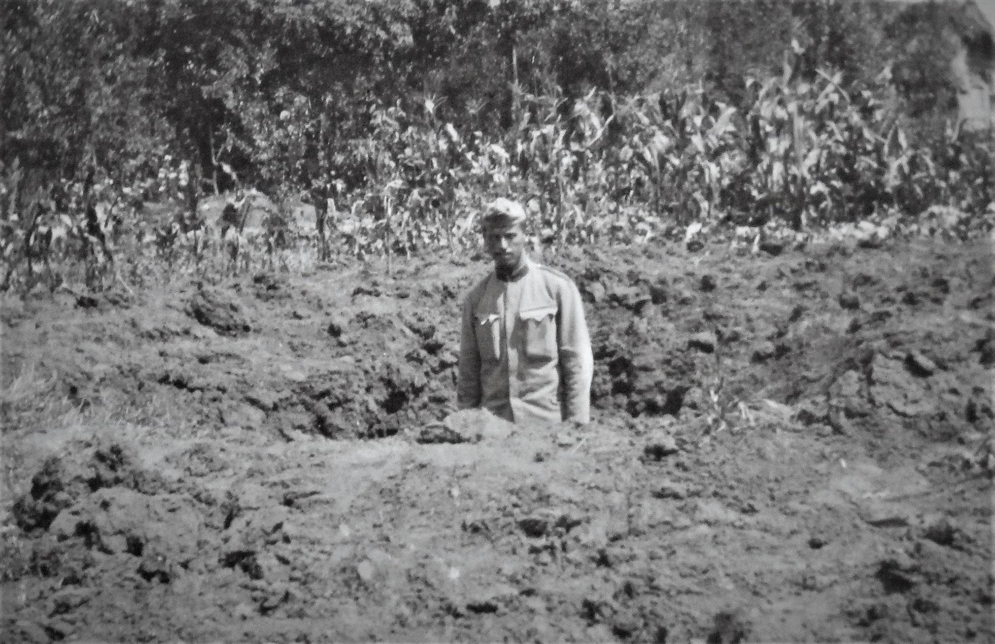 Trichter einer 18 cm Granate in normalem Erdboden. - Im Trichter stehend OffzD. Hofmeister.