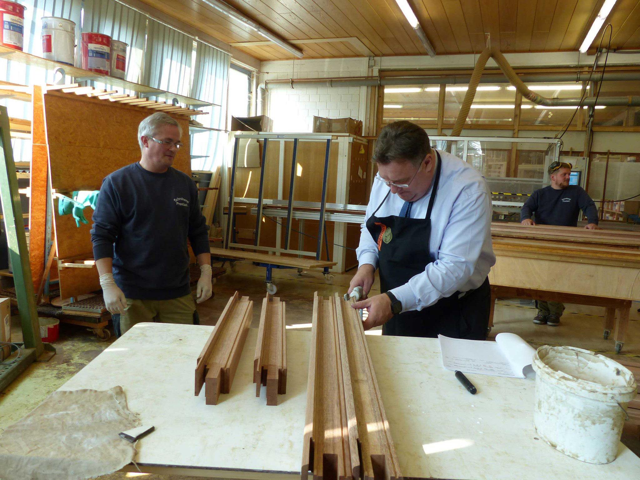 Bei der Schreinerei Prentzel in Fritzlar-Züschen durfte Staatssekretär Mark Weinmeister das Sakko kurz gegen eine Schürze tauschen und einen Rahmen verleimen.