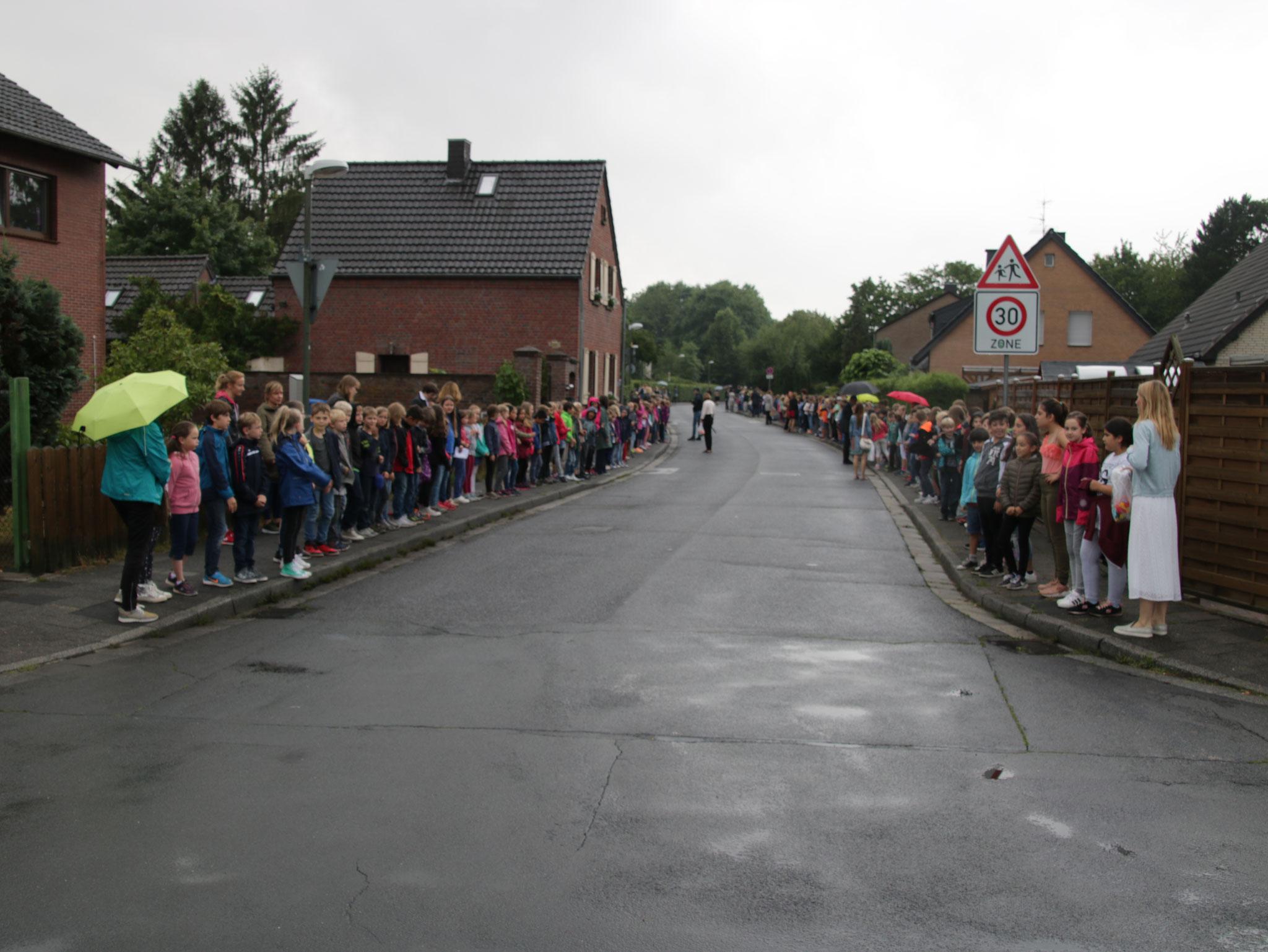 Alle 451 Kinder der St.-Peter Schule stehen am Straßenrand und warten...