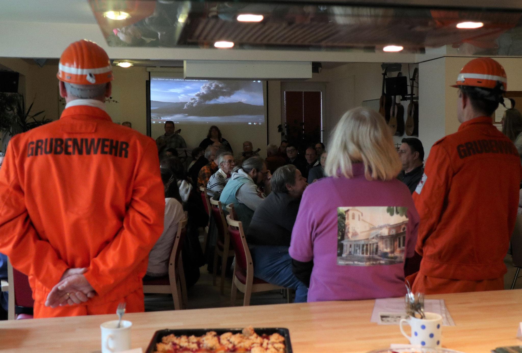 Rezitatoren - auf der Leinwand läuft ein Video vom Bergbau