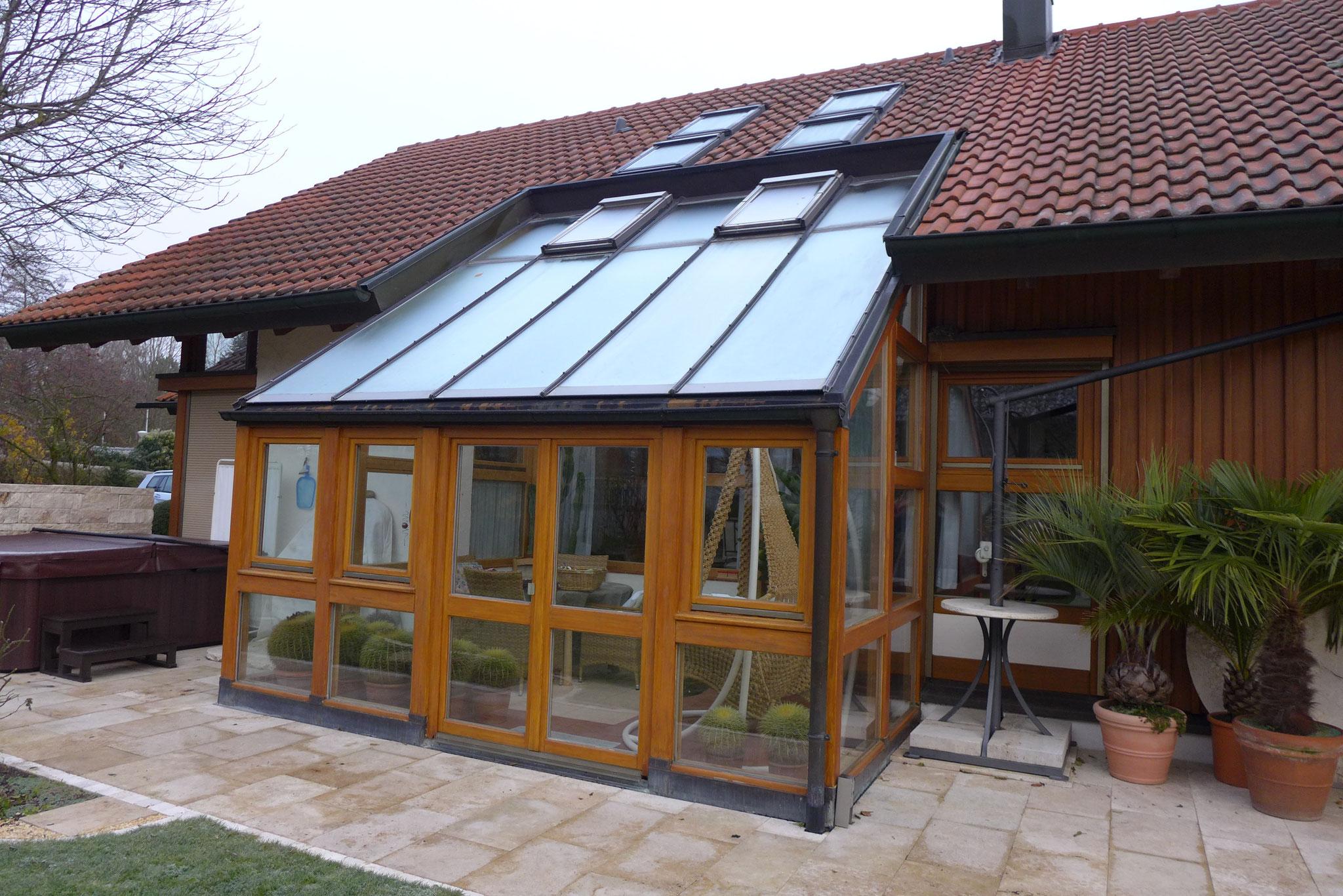 Alu-Wintergarten mit aufgesetztem undichtem Dachfenster, breite Rahmenprofile, schmale Drehtüre als Ausgang