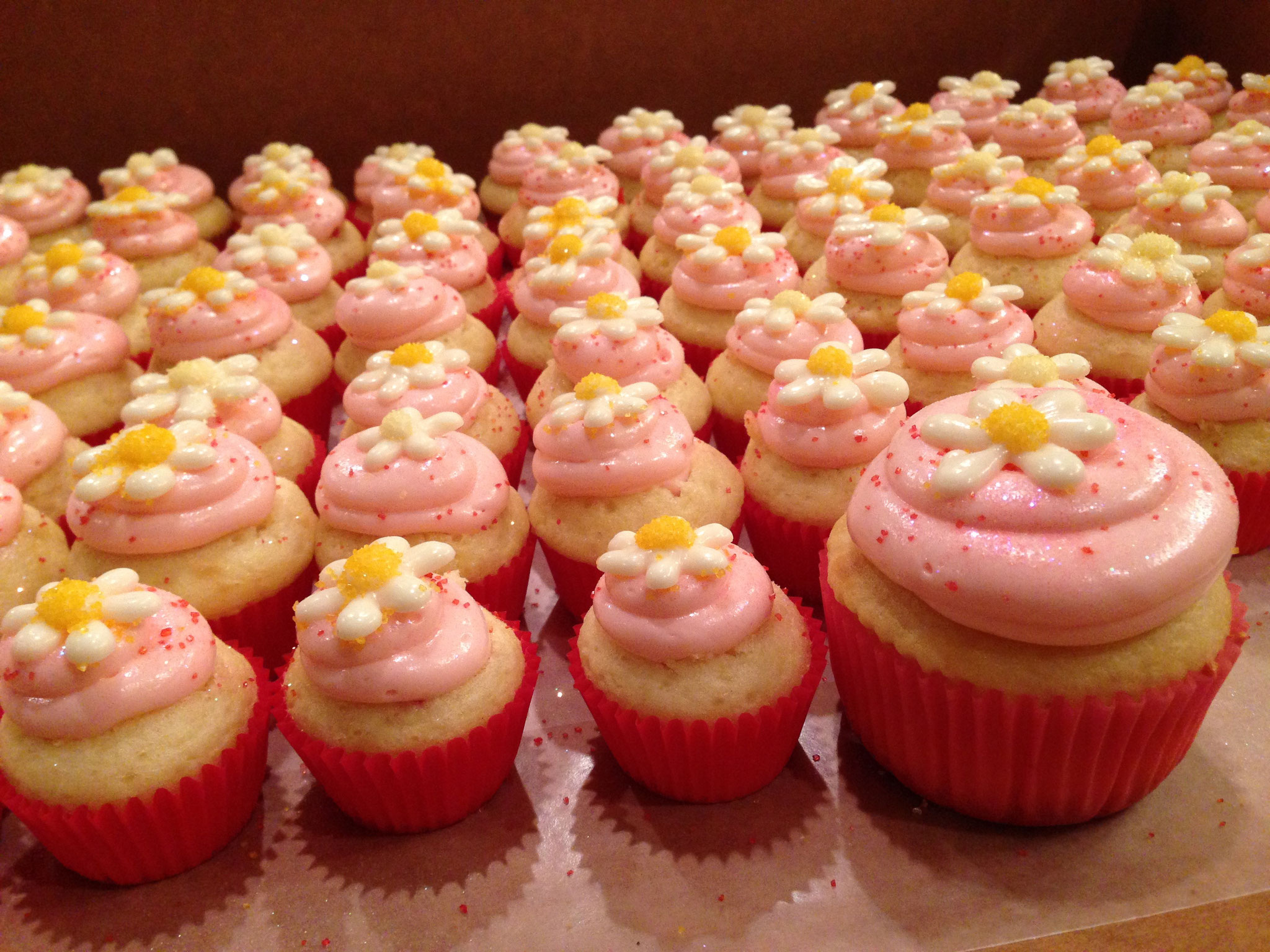 White cupcakes with strawberry frosting and additional decorations