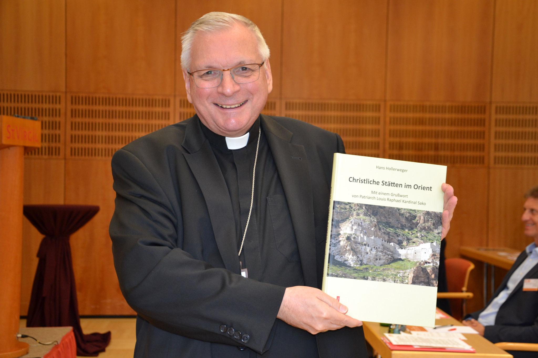 """Bischof Freistetter freut sich über ein kleines Geschenk: Das neue Buch von Prof. Hans Hollerweger über """"Christliche Stätten im Orient""""."""