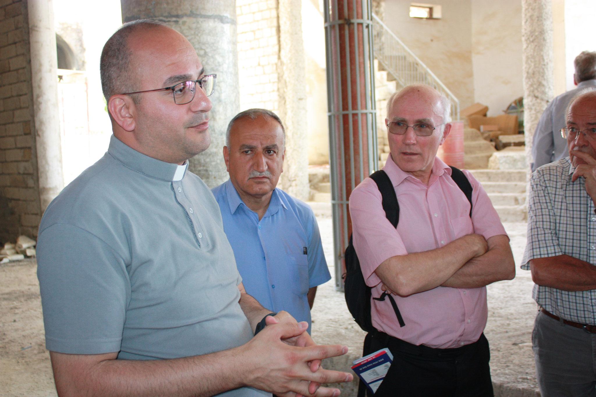 Pfarrer Salar, der chaldäische Priester von Teleskof, erläutert der ICO-Delegation Details zum Wiederaufbau der vom IS zerstörten Jakobskirche