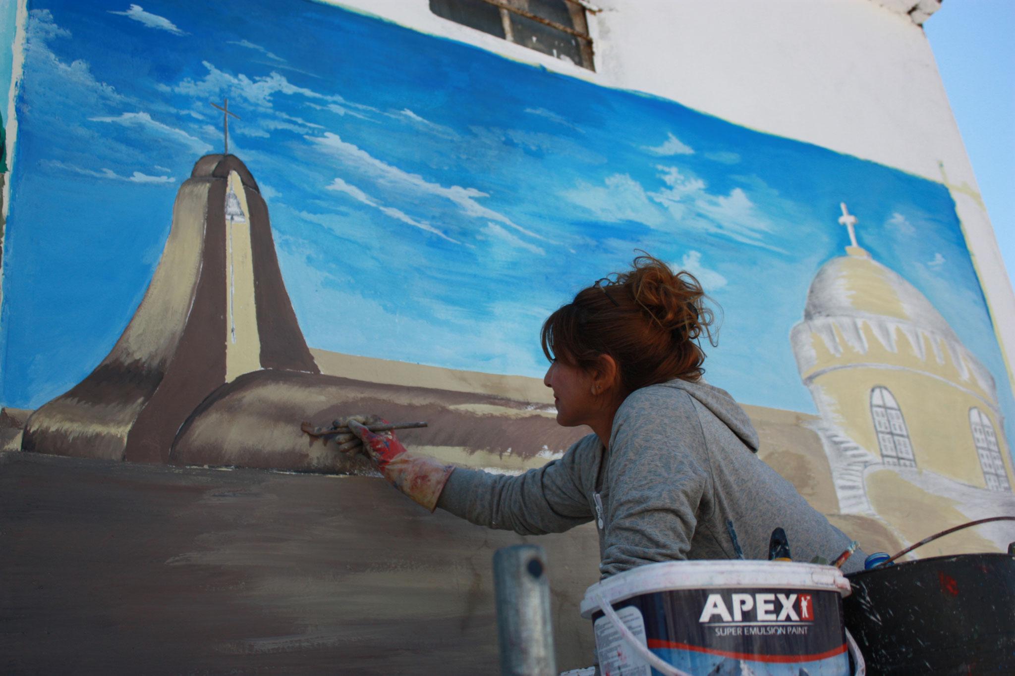 Kunstprojekt in Teleskof - eine muslimische Künstlerin malt eine christliche Kirche an die Wand eines Hauses in dem Ort, der vom IS zerstört worden war