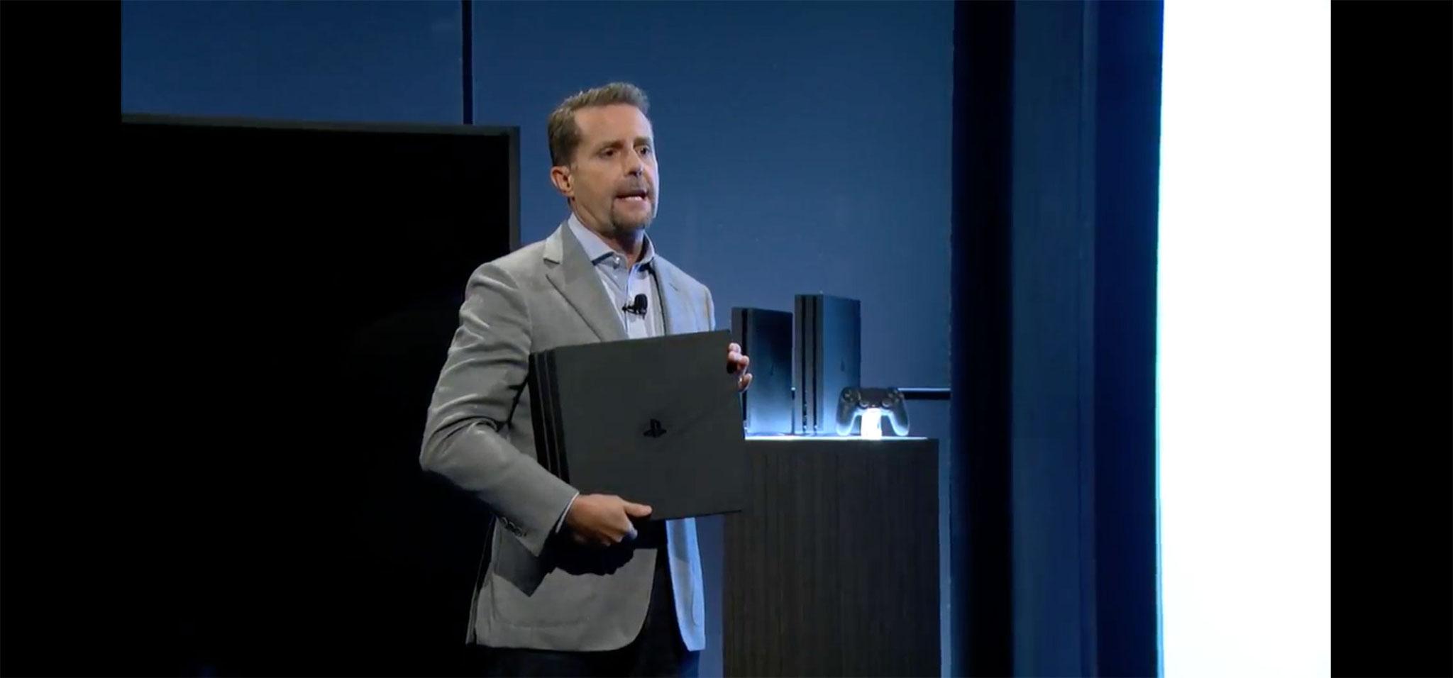 """Dickes Ding: PlayStation-Chef Andrew House mit der überraschend massiven """"PS4 Pro"""" unter dem Arm –hinter ihm ist das Gerät neben dem deutlichen kleineren Modell zu sehen, das ab dem 15.09. die bisherige PS4 ersetzt."""