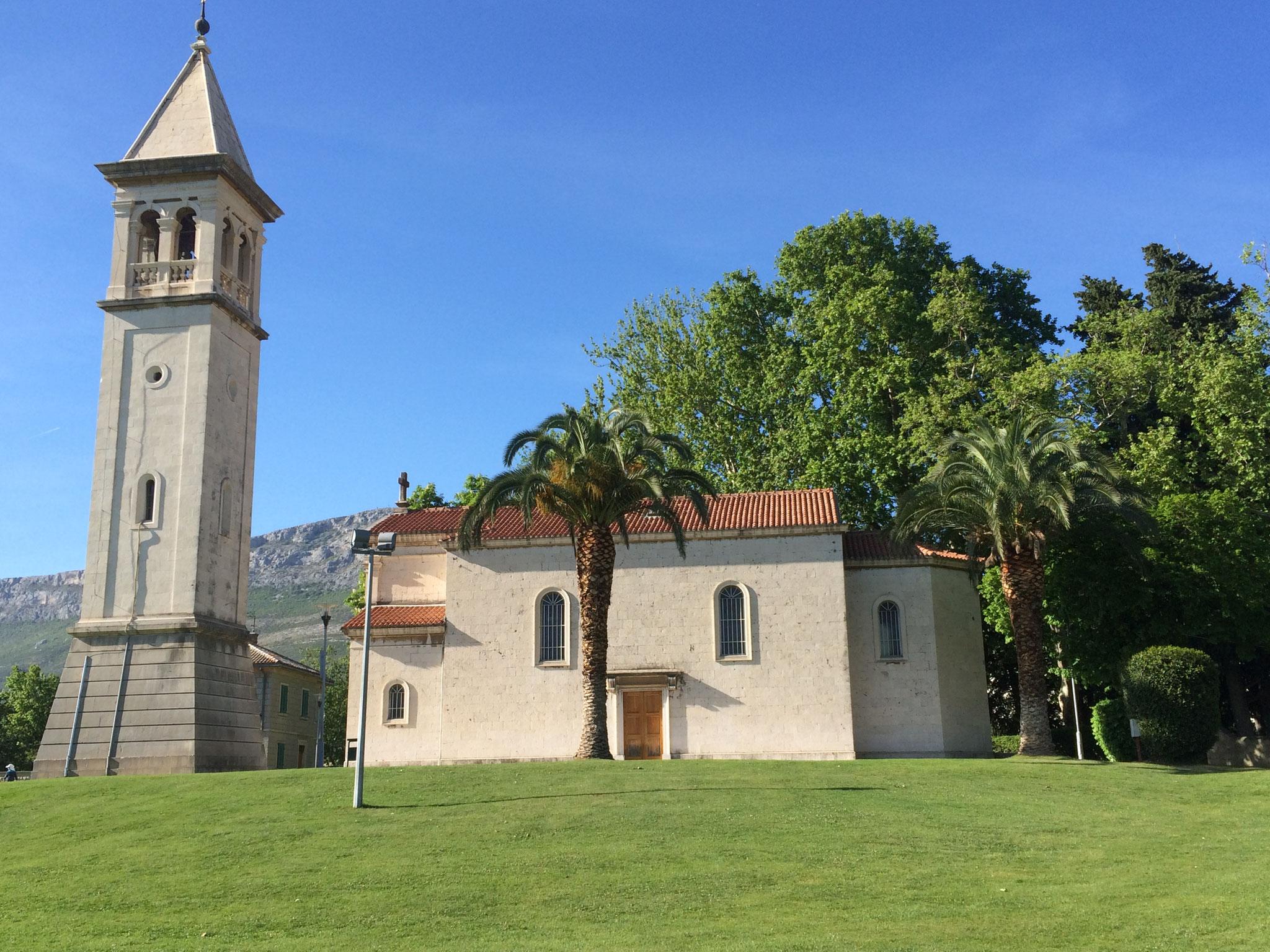 Schöne Kirche in Salone mit mächtigen Palmen.