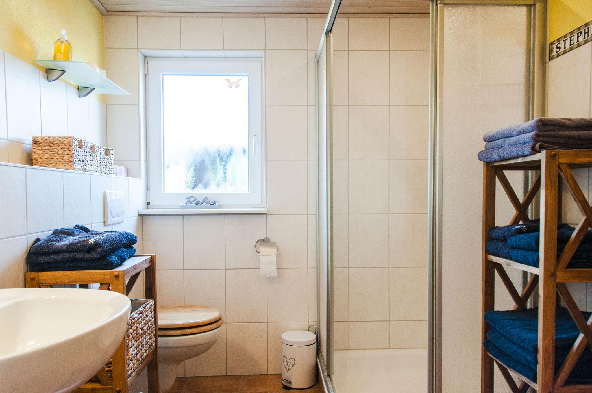 Das helle Badezimmer mit Dusche, Waschtisch und WC