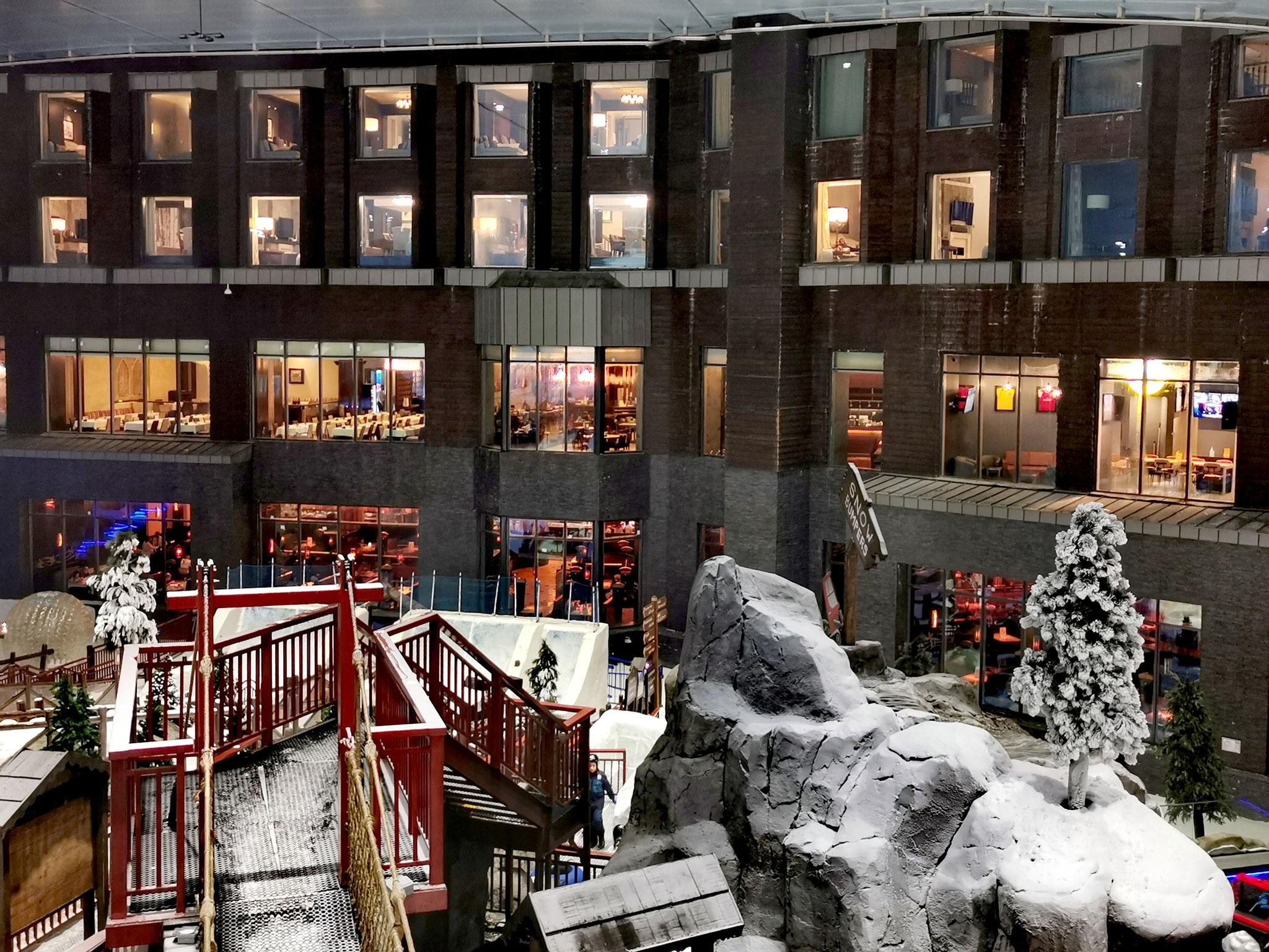 """In den oberen Stockwerken befinden sich die """"Ski Chalets"""" des Kempinski Hotels mit Blick in die Skihalle"""