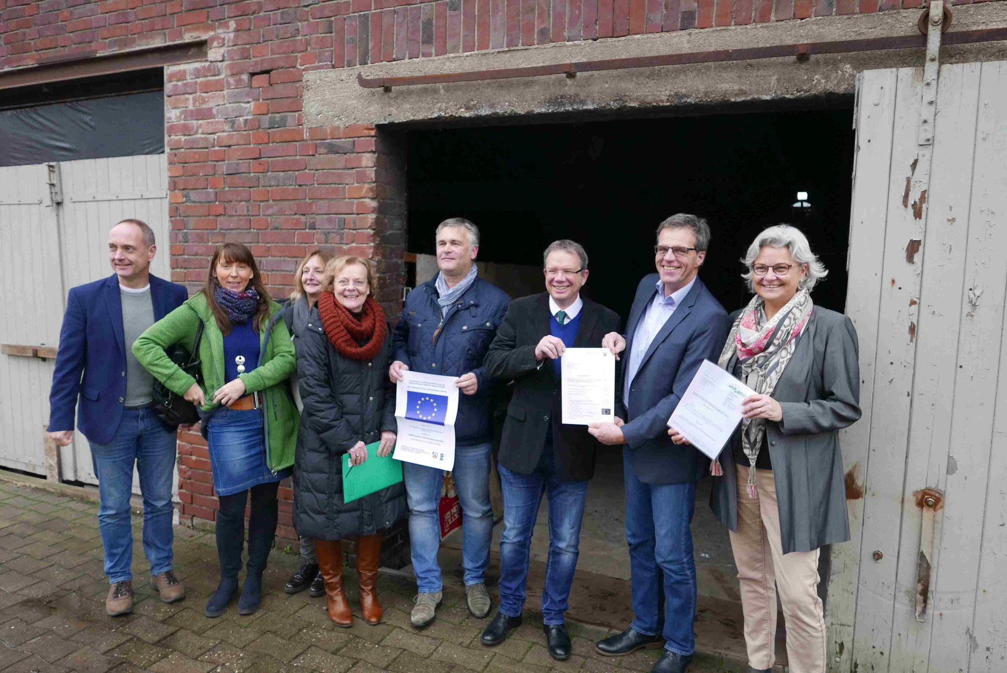 Martin Althoff (2.v.r.) nahm den Bewilligungsbescheid für die LEADER-Förderung des Baus eines Multifunktionsraums auf dem Alten Hof Schoppmann von Annette Hülsmann (4.v.l.) von der Bezirksregierung Münster entgegen. Foto: projaegt