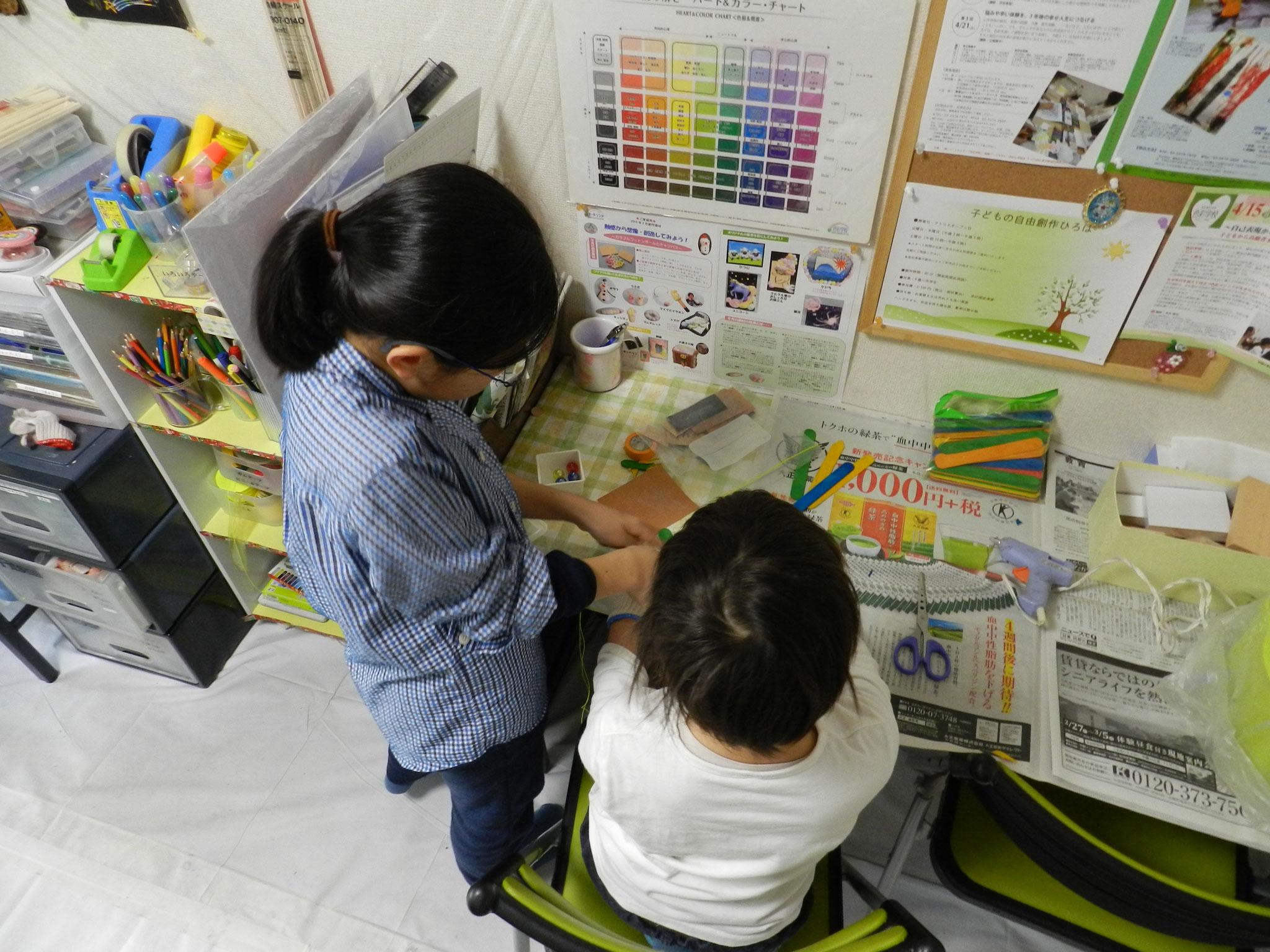 上級生のお姉ちゃんに飛行機の作り方を教えてもらっている様子(小学4年・小学1年)