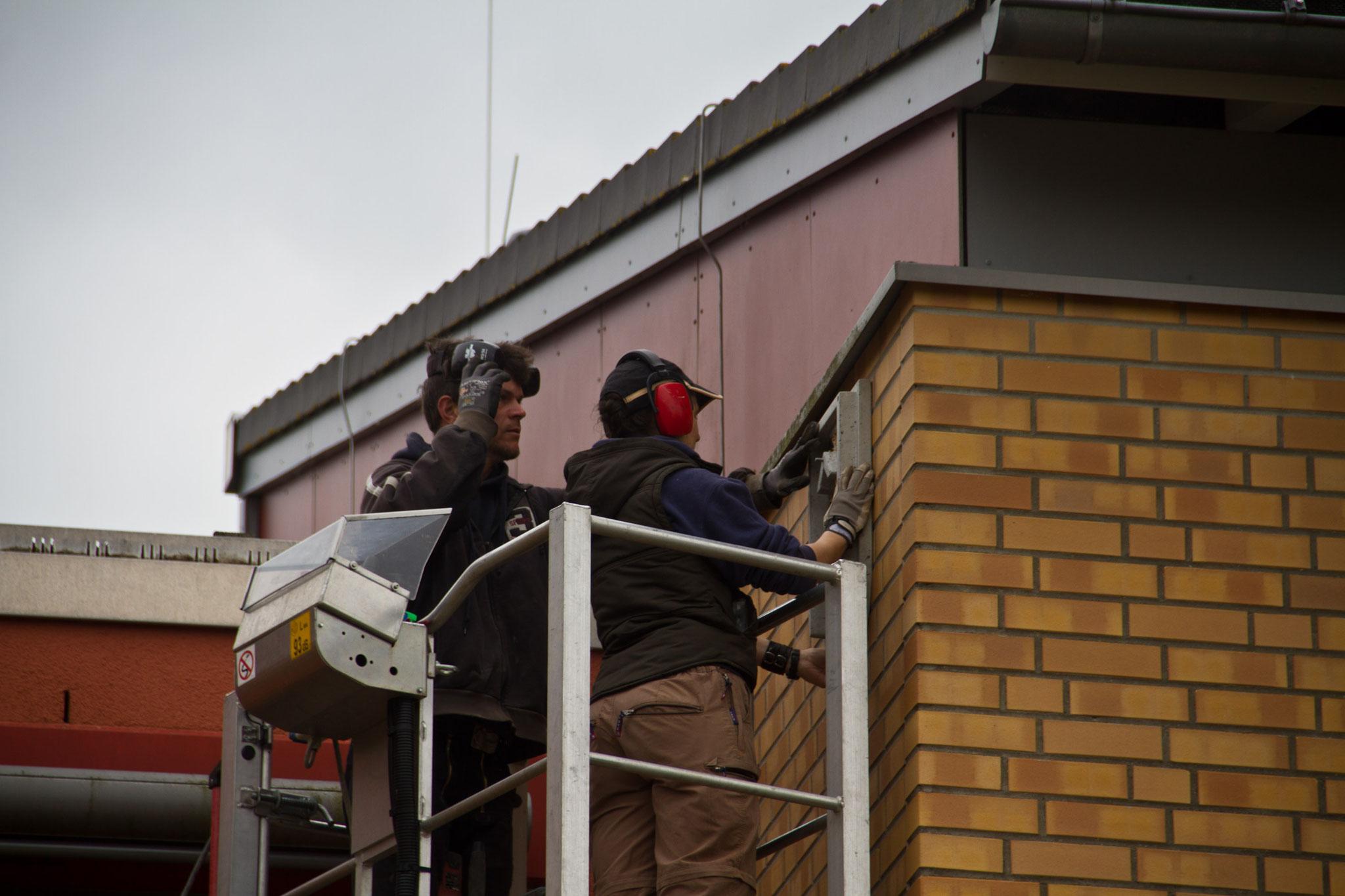 ... bringen drei Fledermauskästen an der Werkstattschule in der Südstadt an.