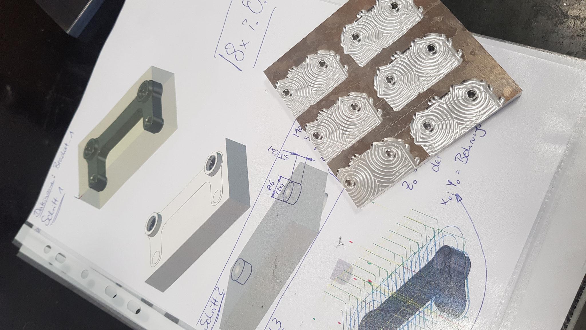 Notizen unserer qualifizierten Zerspaner für die korrekte Weiterbearbeitung der Komponenten in der Anlage. Auf der rechten Seite die Halbfertigteile aus 7075 T6.