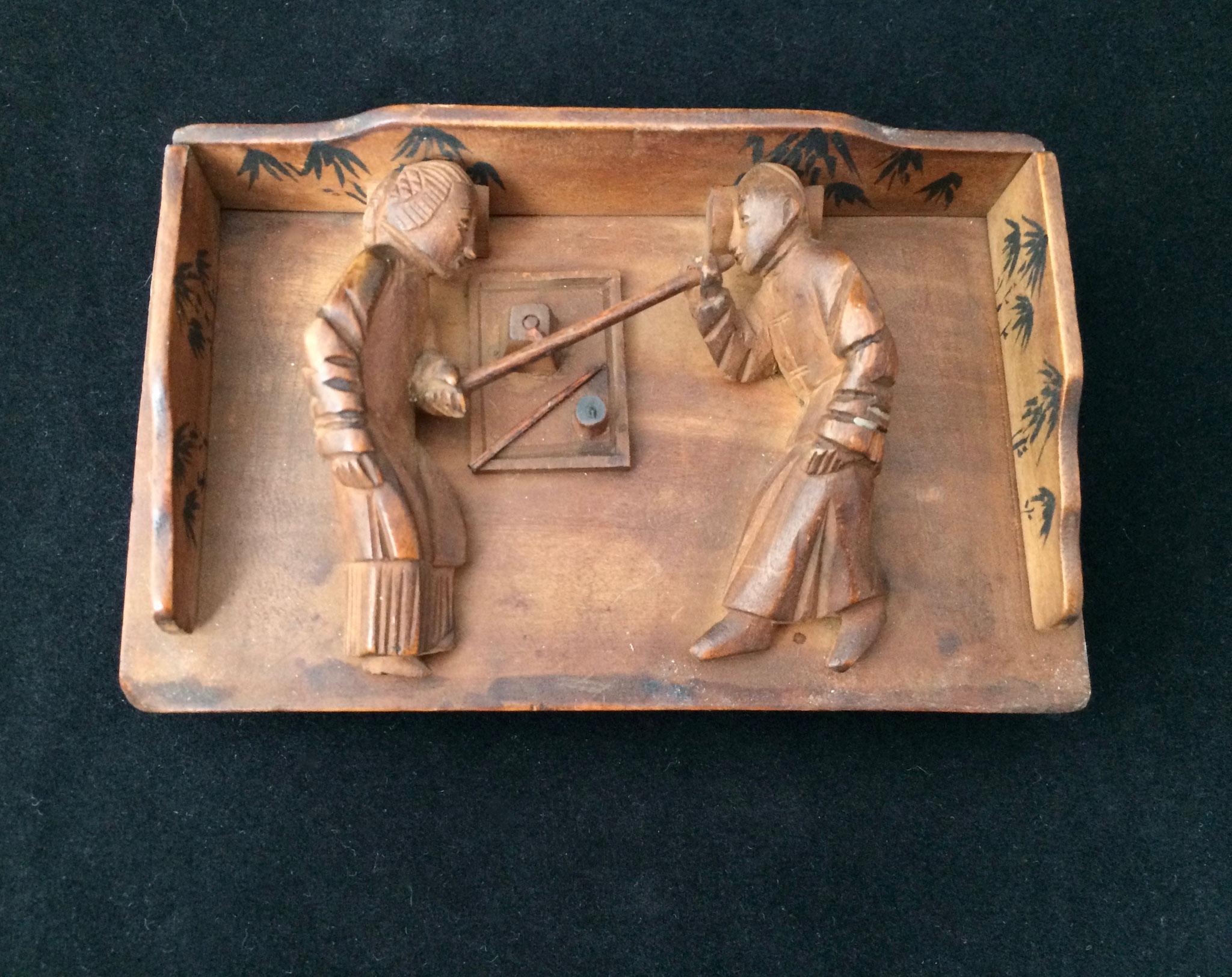 Scène de fumerie en bois sculpté (–> Livres et documents)