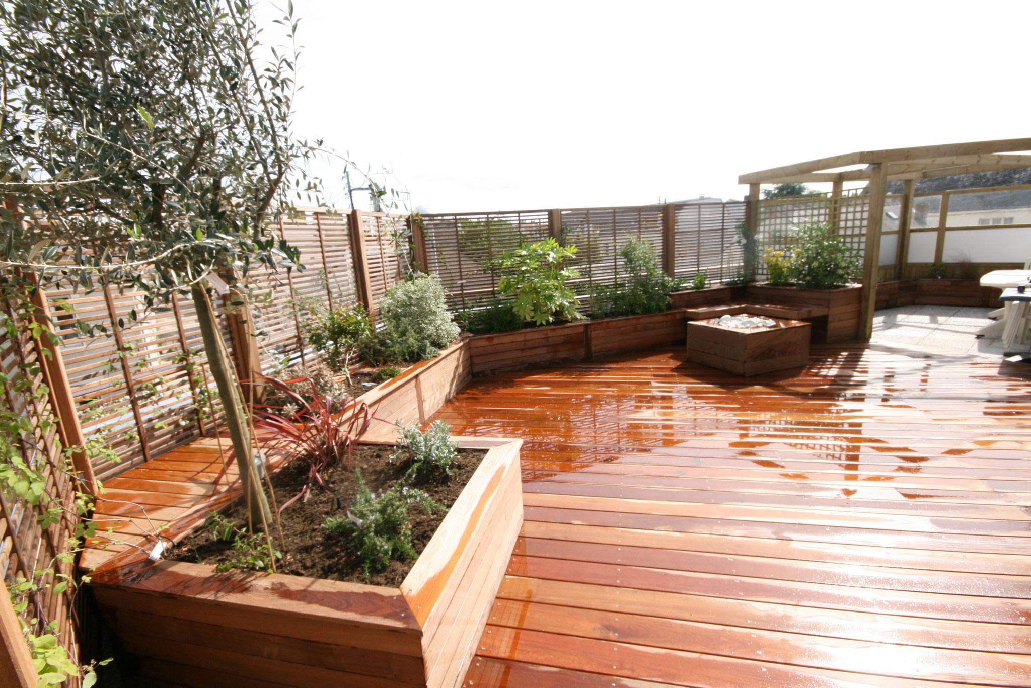 Terrasse en bois exotique avec bacs sur mesures, pergola et brises vues