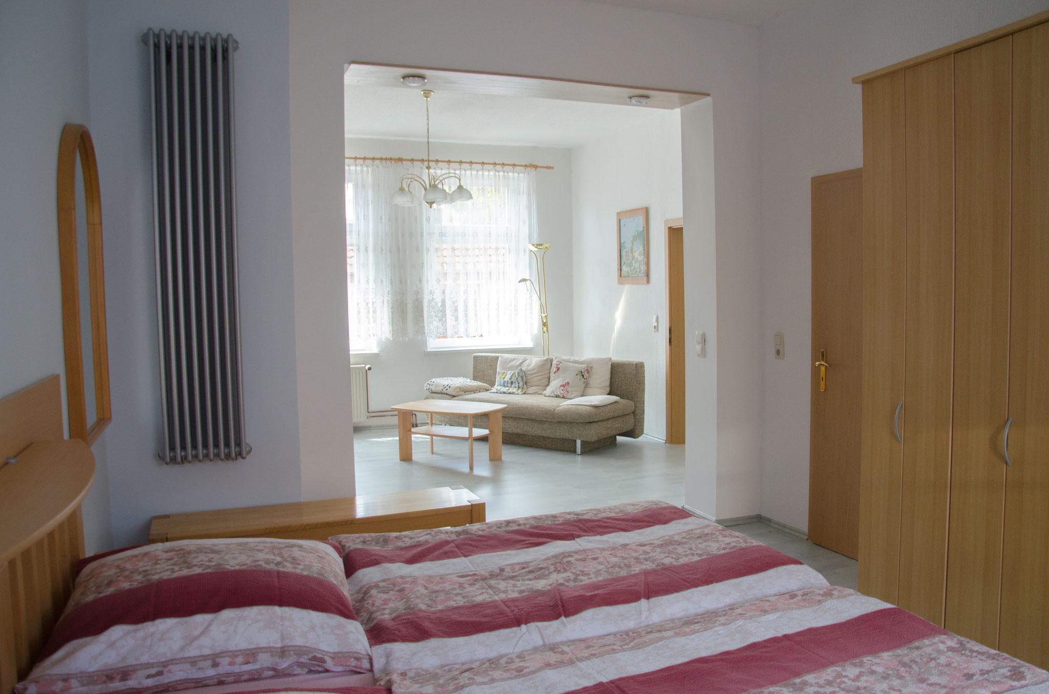 Schlafzimmer mit Durchgang ins Wohnzimmer
