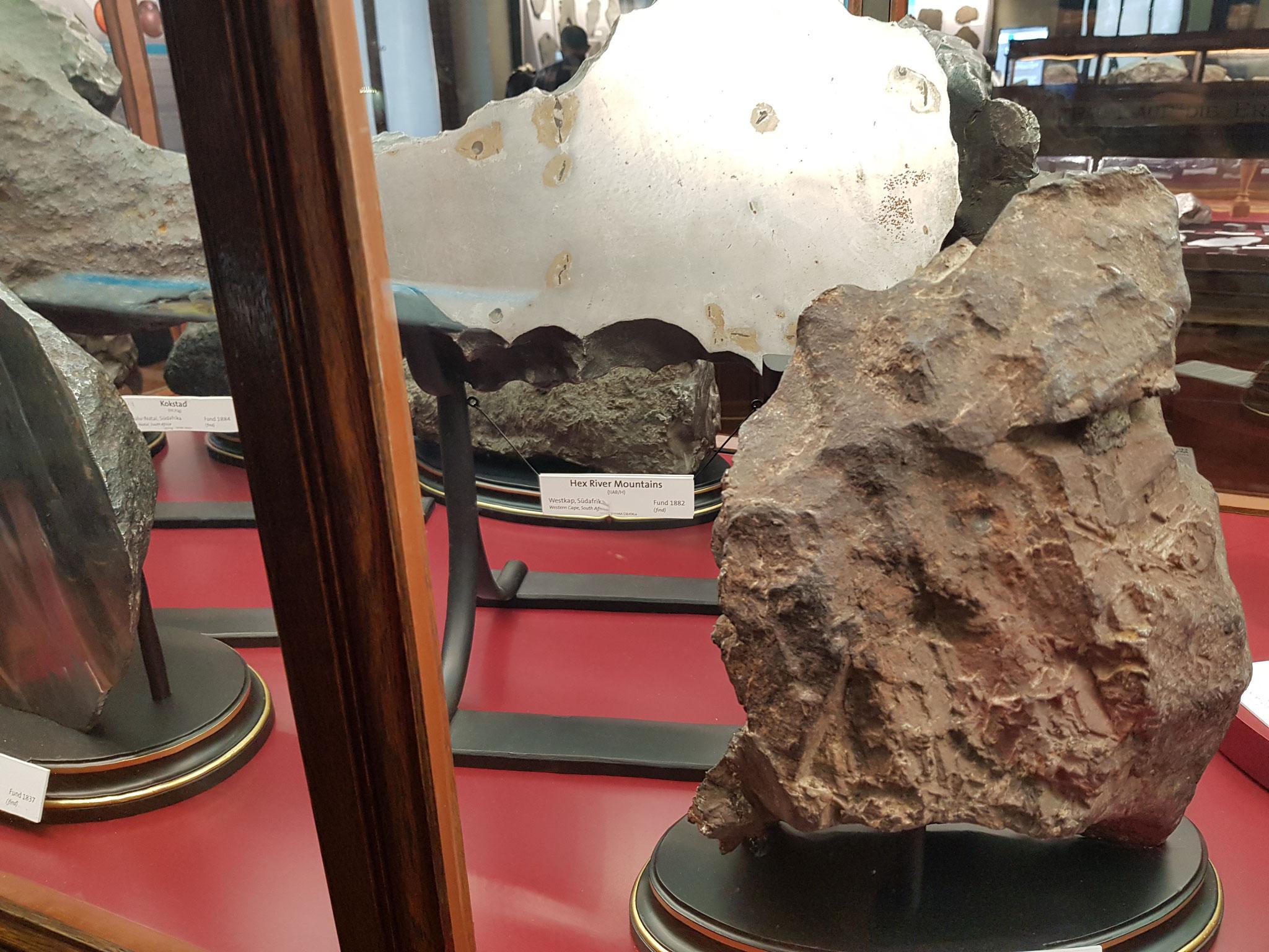 Abbildung 2. a.: Verschiedene Meteorite aus der Sammlung des Naturhistorischen Museums Wien (eigene Aufnahme)
