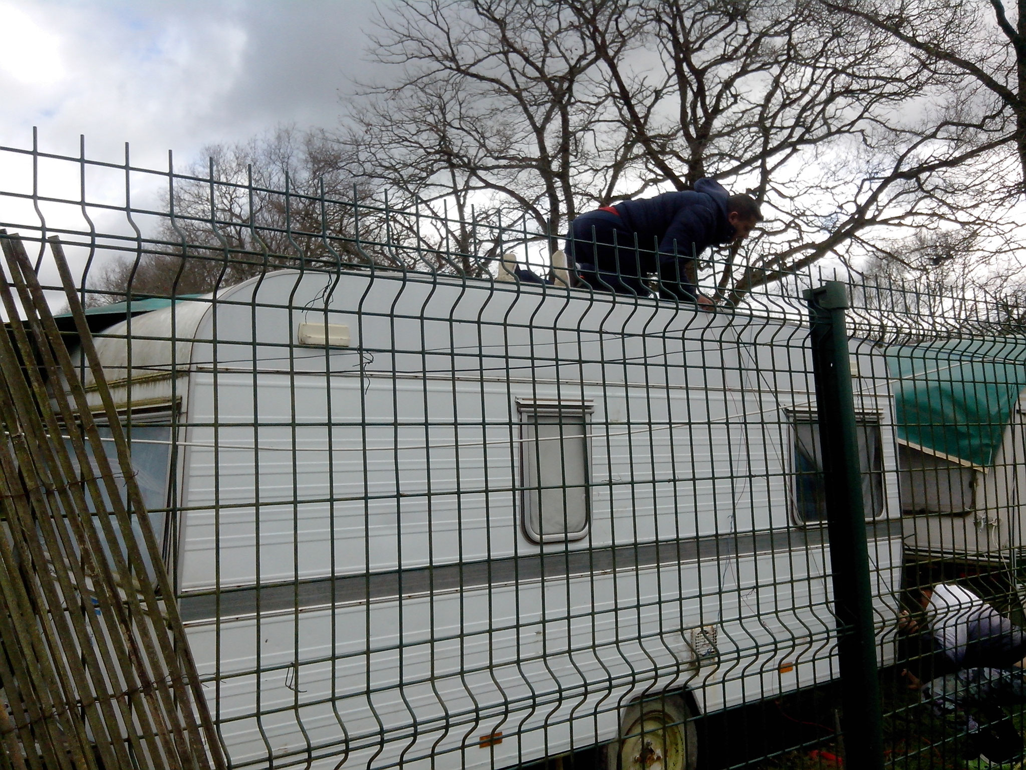 Marinica en haut de sa caravane et Diana en bas retendent les attaches
