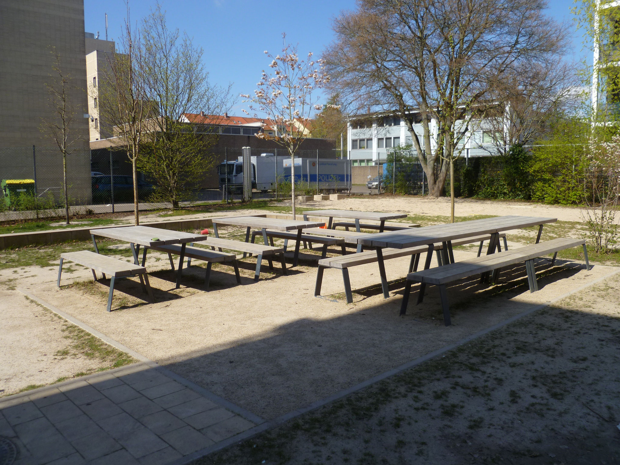 Der Schulhof bietet viele Möglichkeiten: Man kann an Tischen sitzen, ...