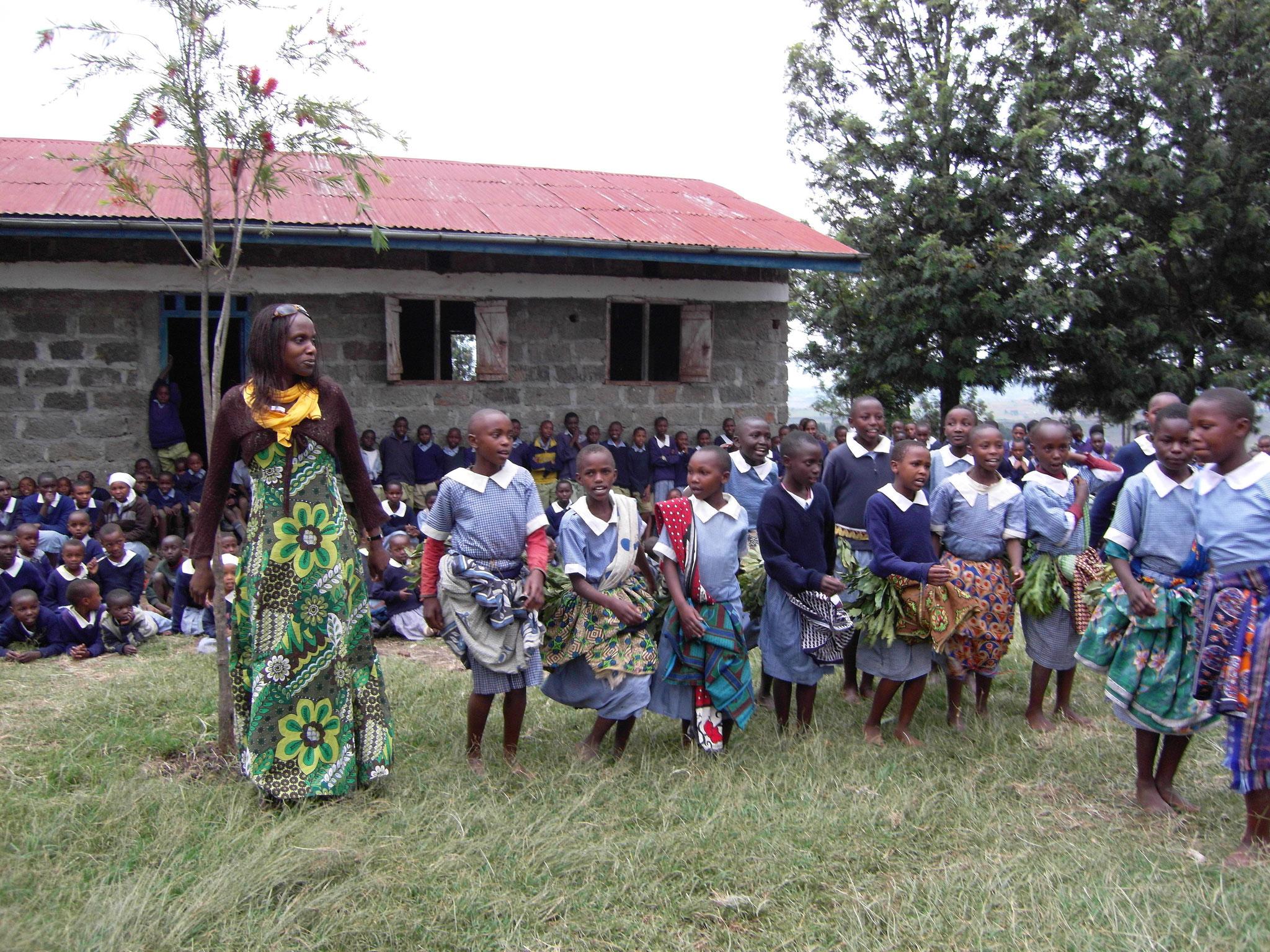 Helen tanzt mit Kindern an ihrer Heimatschule, der Kabati Primary School
