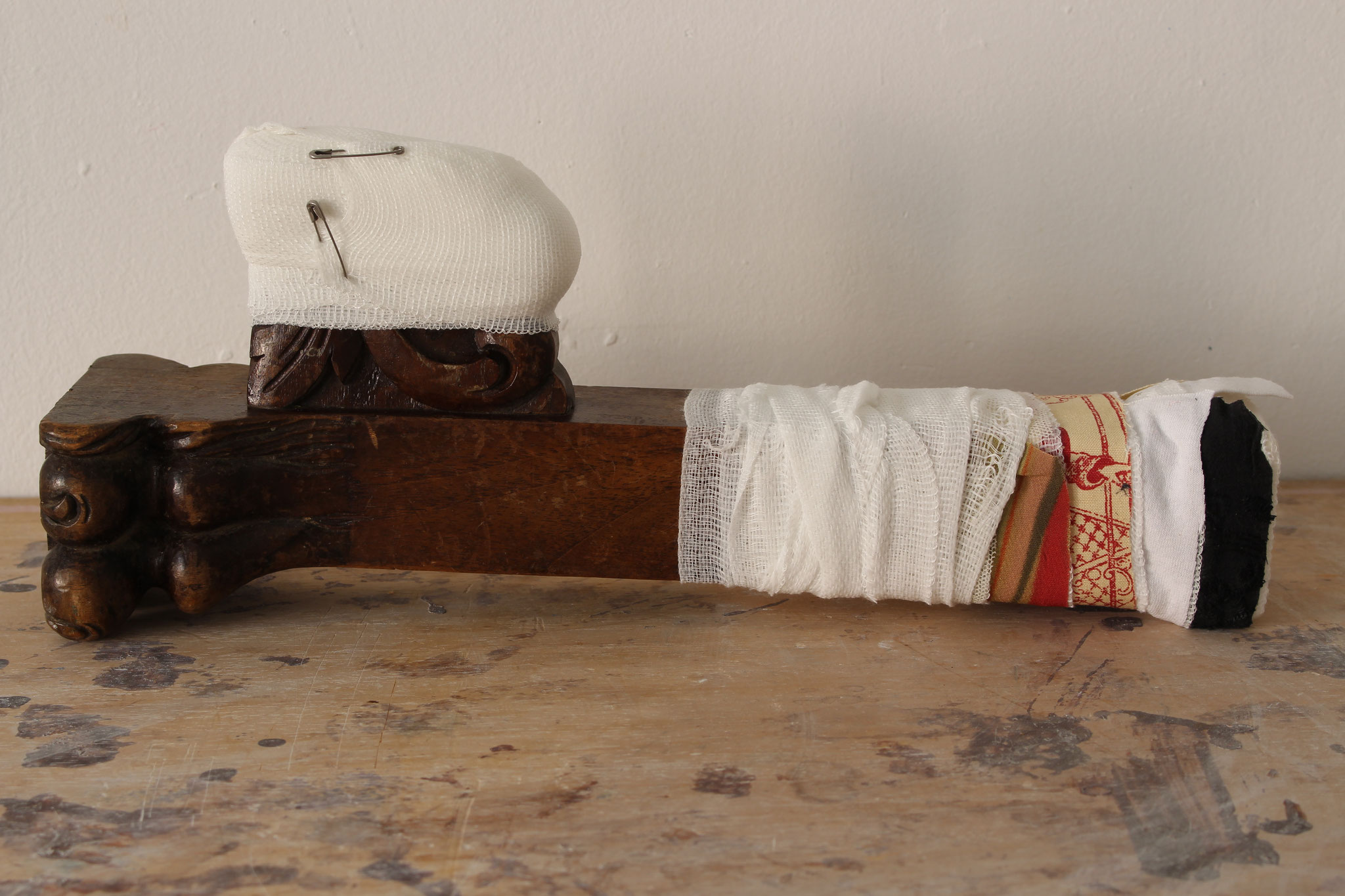 """Eva Hradil """"amputiert / amputó"""", 2017, geschnitztes Nussbaumholz eines Thronsessels aus Historismus, Teile von Kleidungsstücken, Verbandmull, Sicherheitsnadeln"""