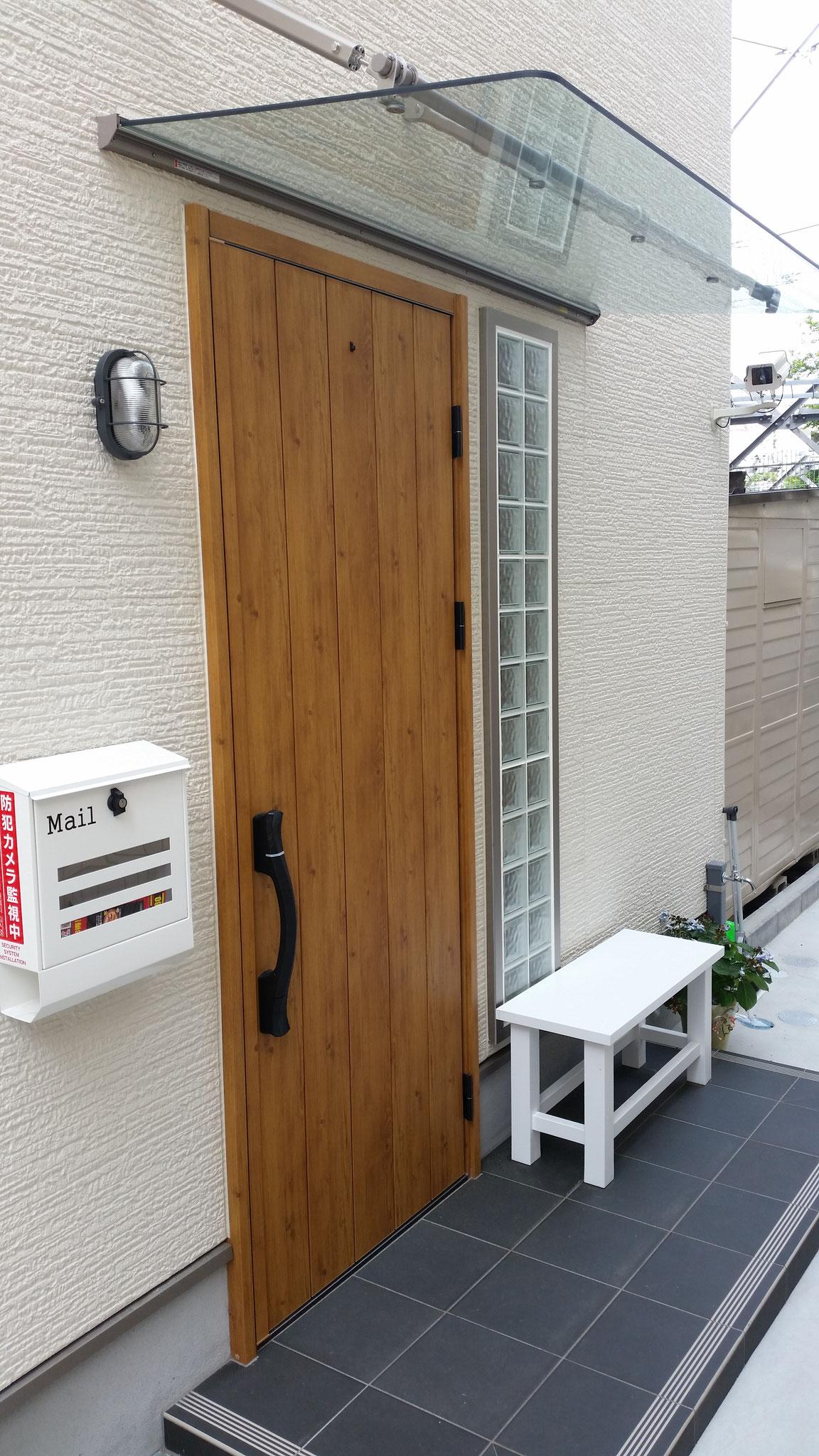 玄関は、白いベンチと大きな扉が目印です