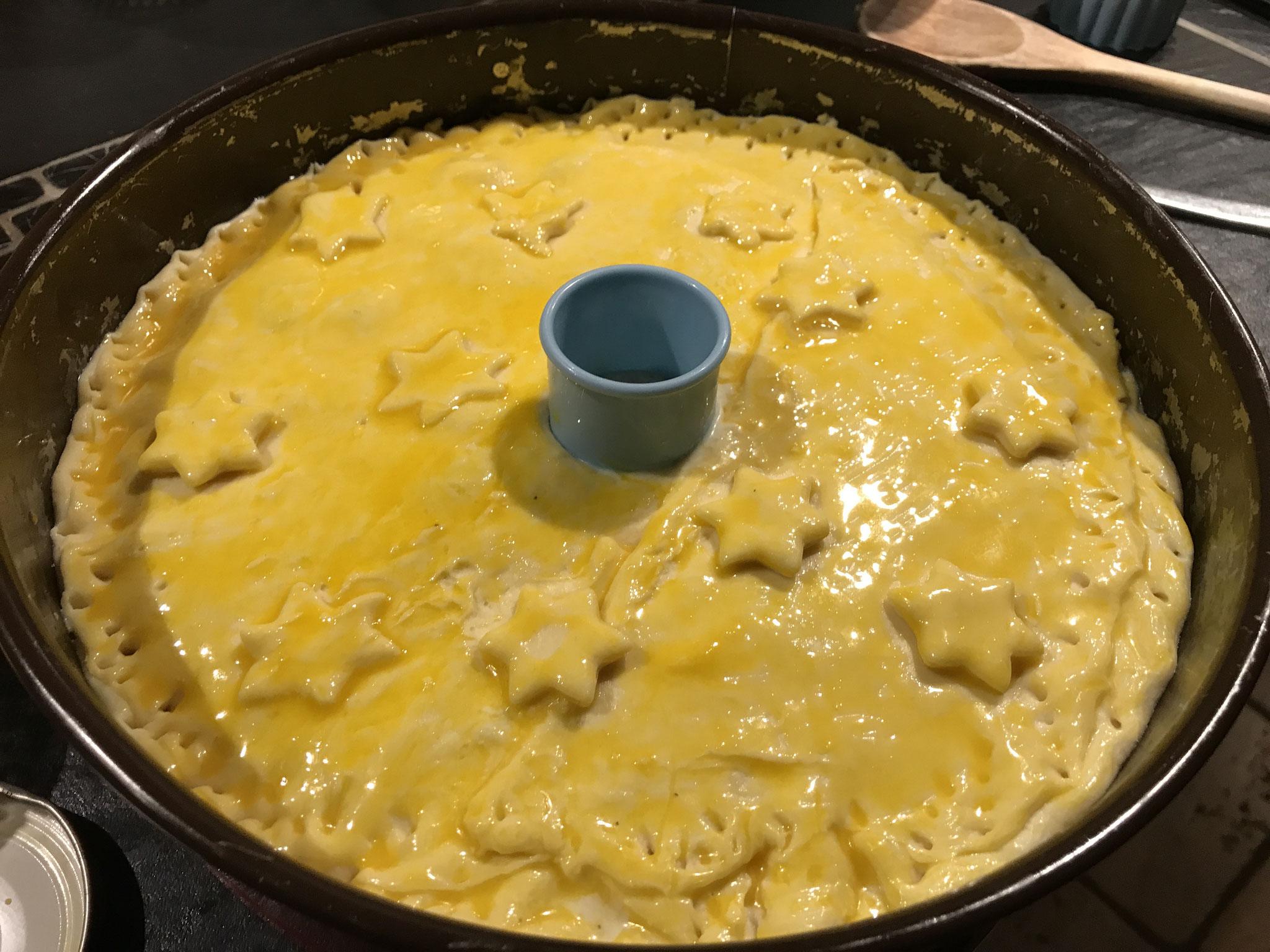 couvrir avec la deuxième pâte en laissant un petit trou au milieu (cheminée), coller les bord avec un peu d'eau, dorer au jaune d'oeuf