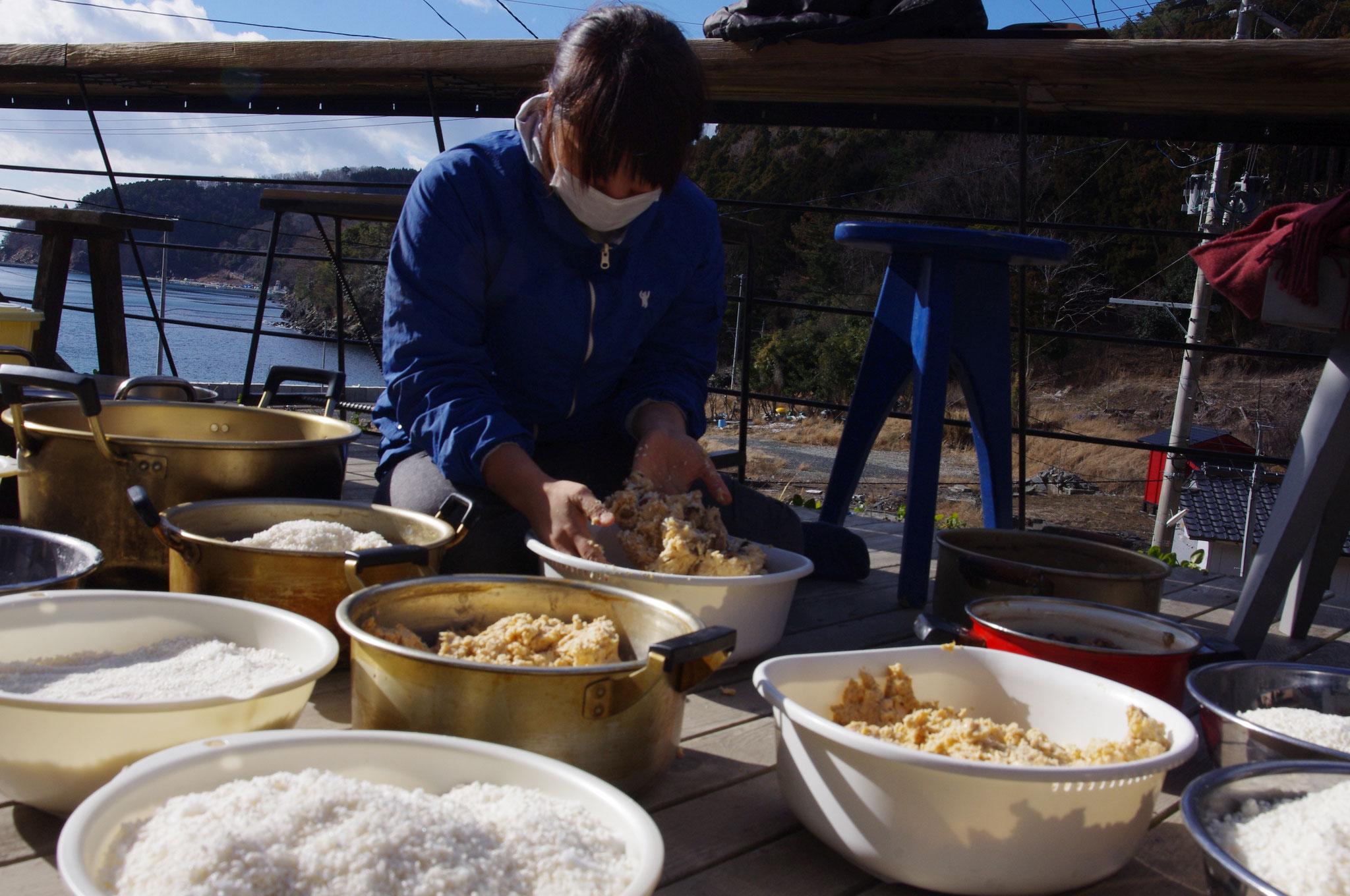 つぶし終えた大豆のペーストと、色とりどりのお豆、豆の煮汁、米麹、塩をすべて手でよく混ぜあわせていきます。