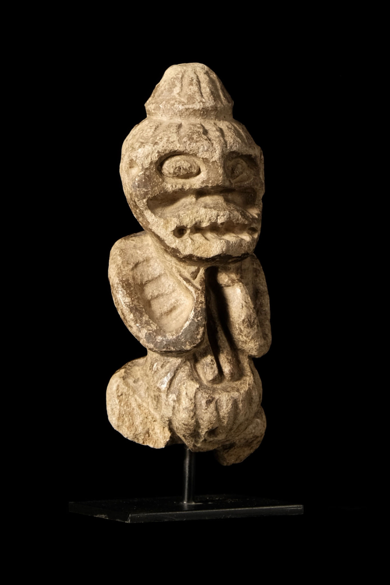 Small Mambila stone figure, both hands leading to the chin.