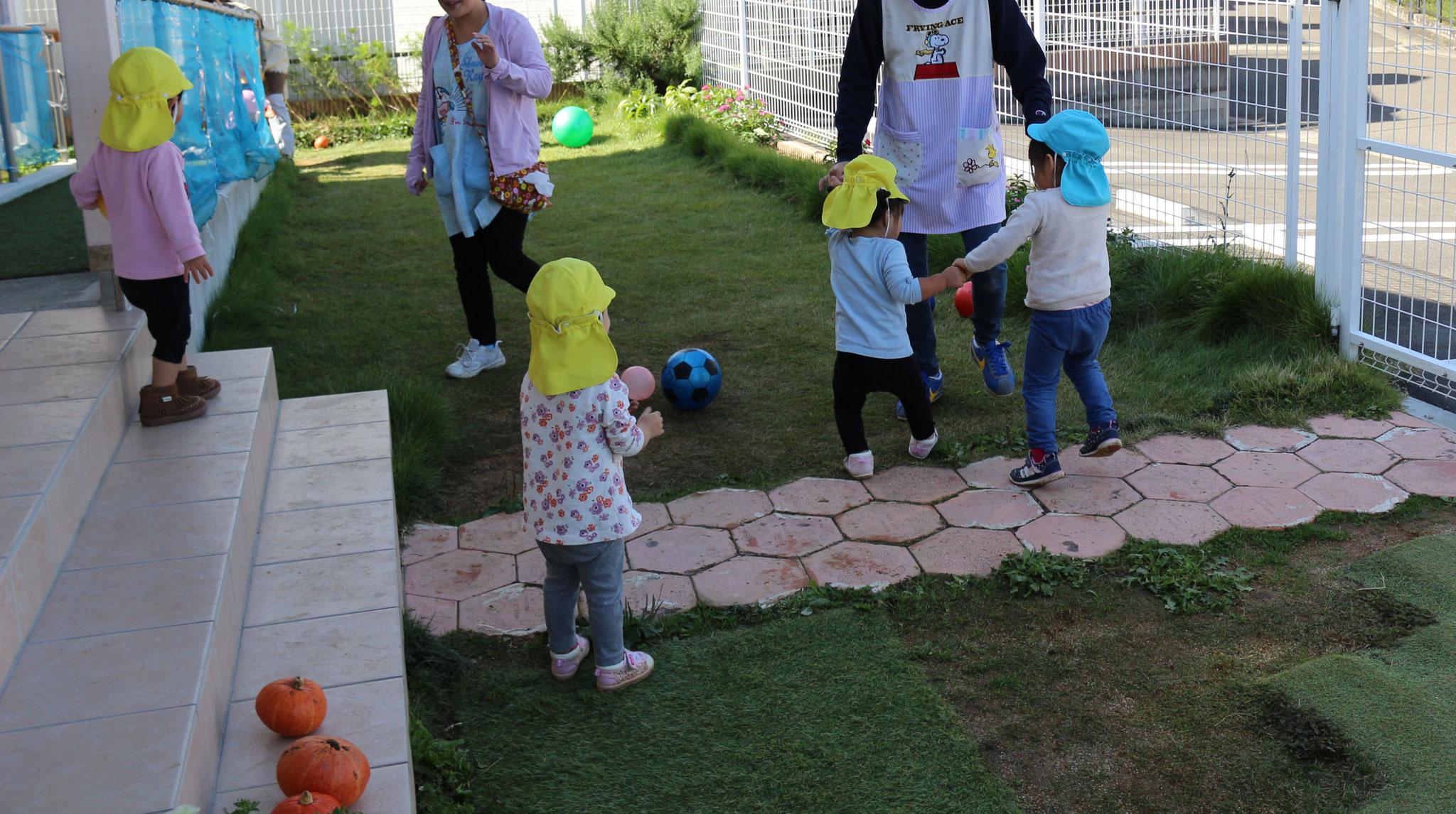 園庭で先生と仲良く遊ぶ姿