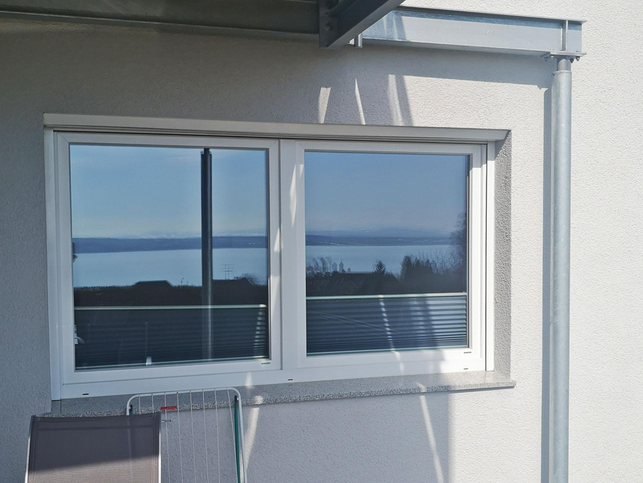 gespiegelter Seeblick im Fenster