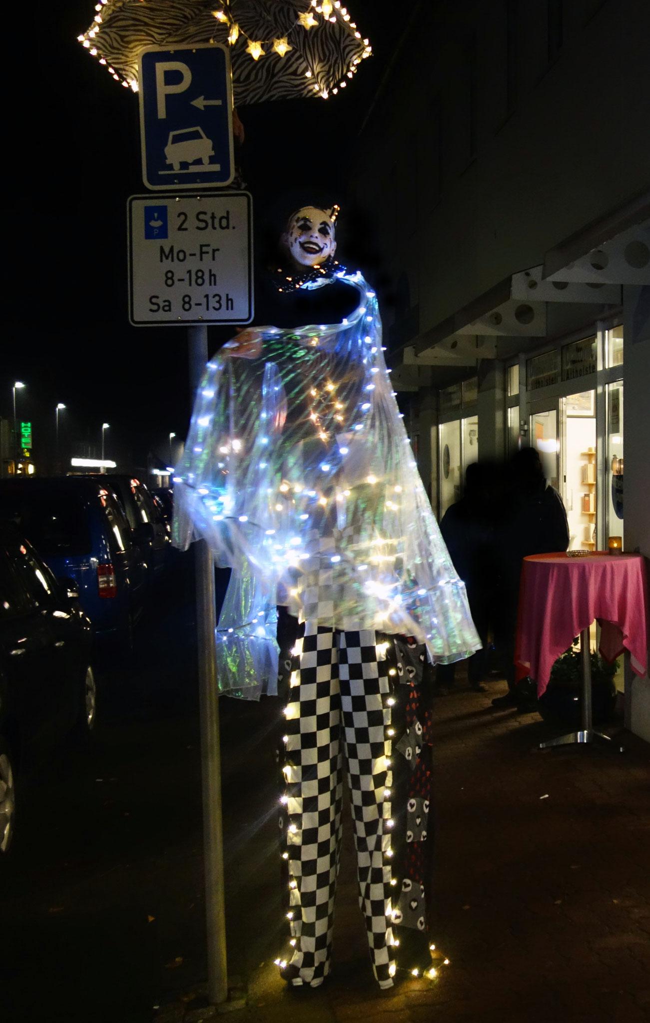 So beleuchtet man ein Straßenschild richtig: Stelzenlauf mit Lichtern.
