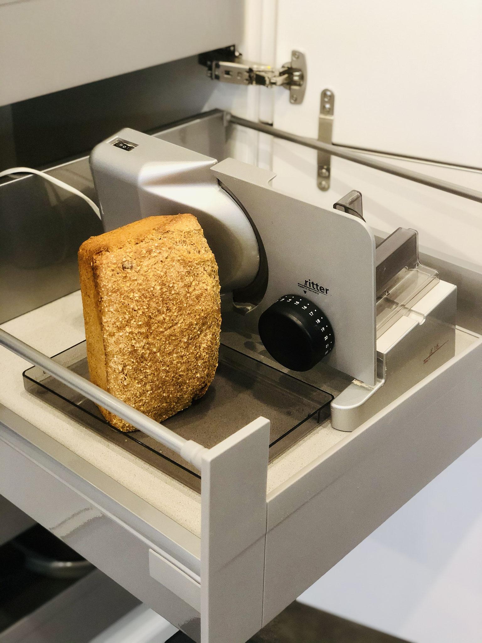 Mein Brot liegt mit der Anschnittfläche auf dem Brettchen von der Schneidemaschine ...
