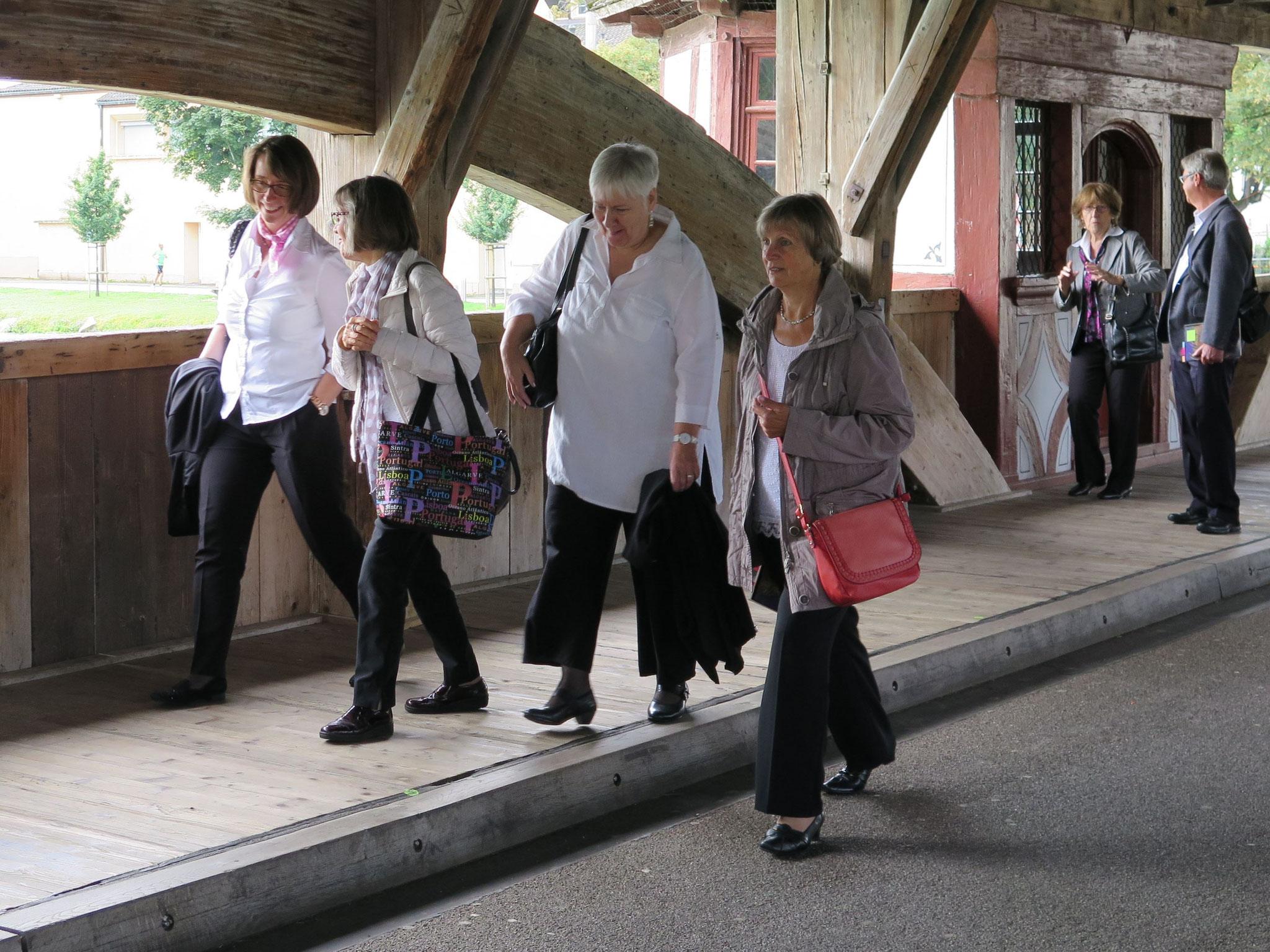 Schon gut gelaunt geht es durch die Holzbrücke Richtung Kirche.