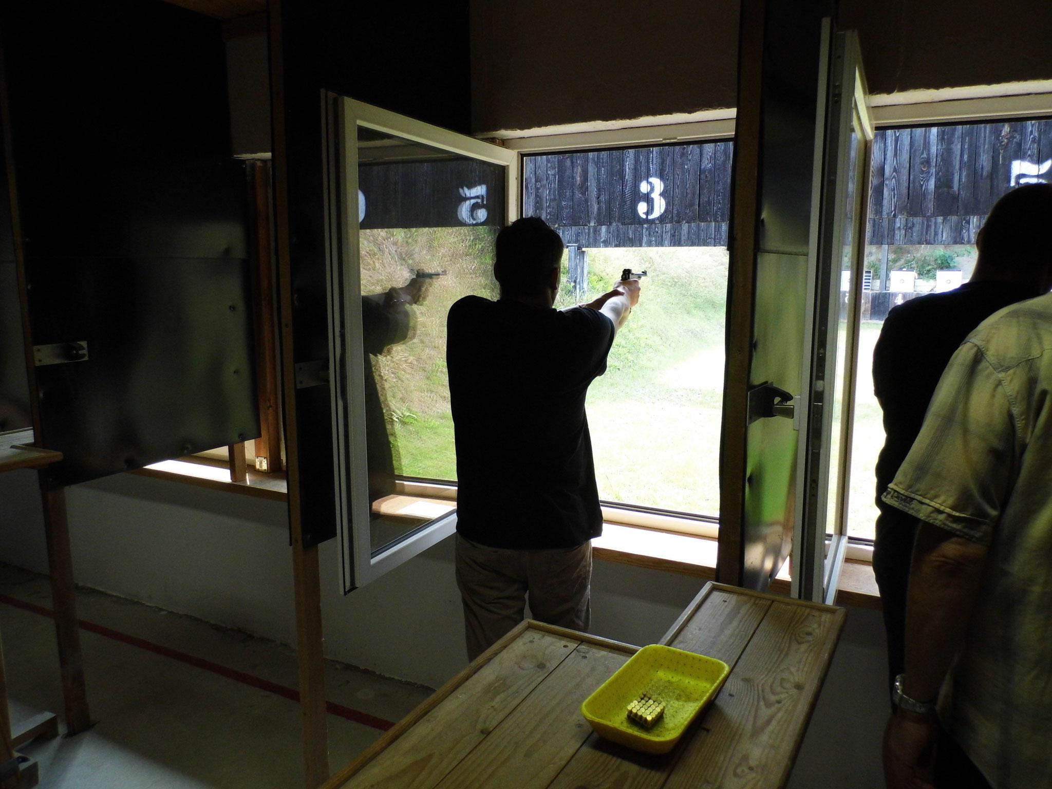Zielen und schießen mit einer KK-Kurzwaffe auf der 25 Meter Bahn.