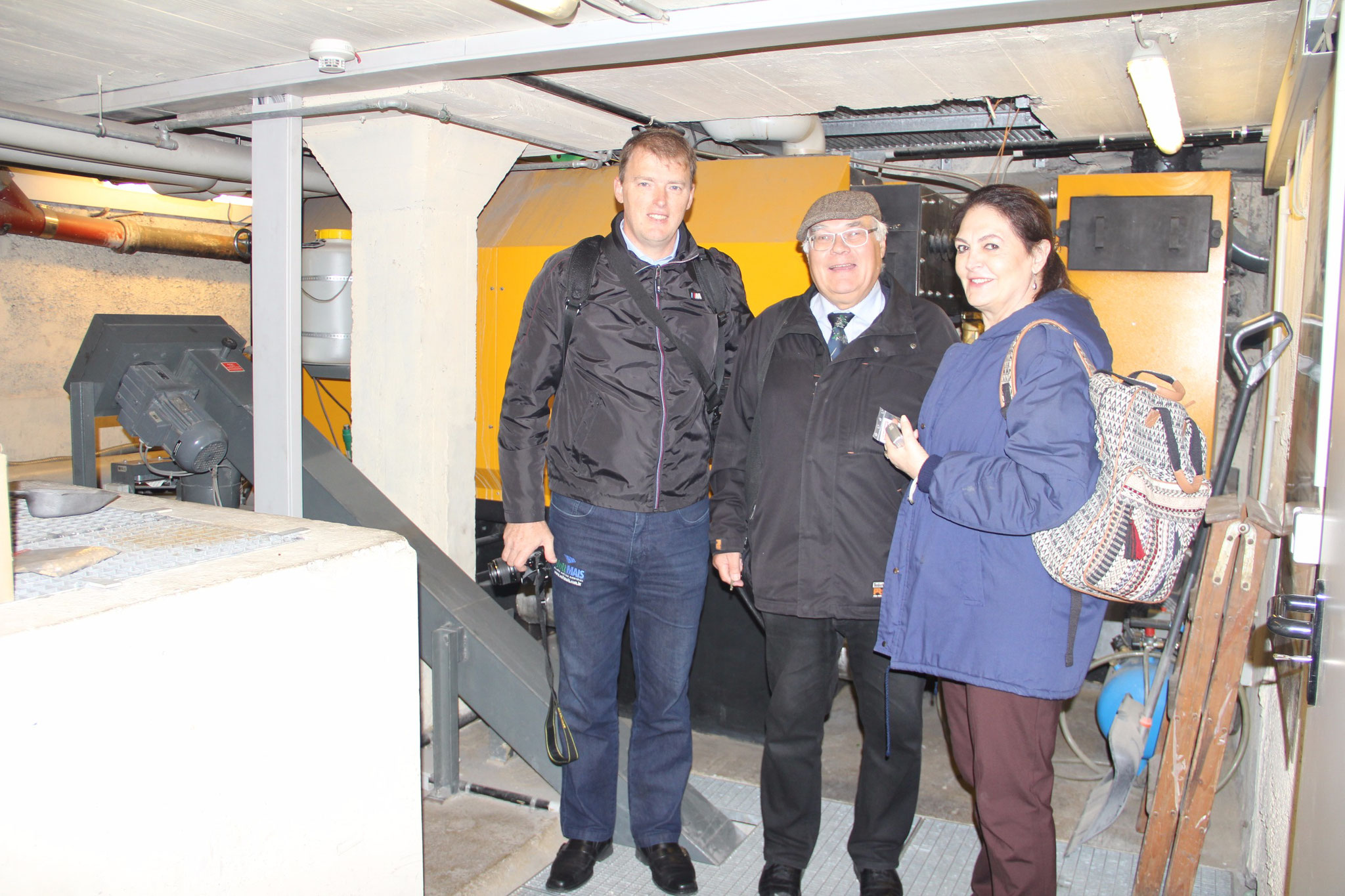 Julio Müller, Erhart Schulz and Cibeli Monteverde visiting the basement of the Hotel Victoria, where they have a biomass plant.