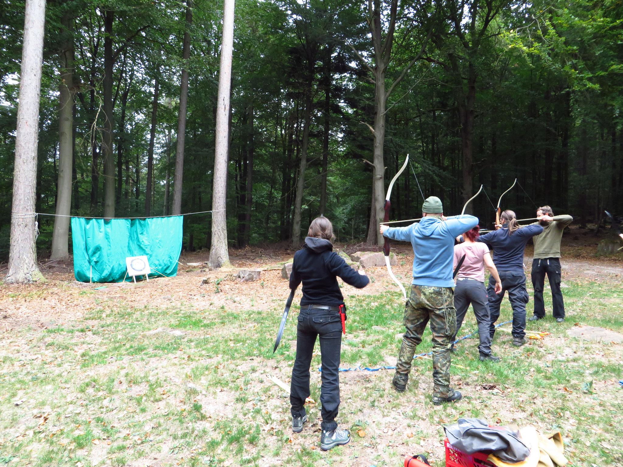 Ein echter Waldläufer schießt mit Pfeil und Bogen.