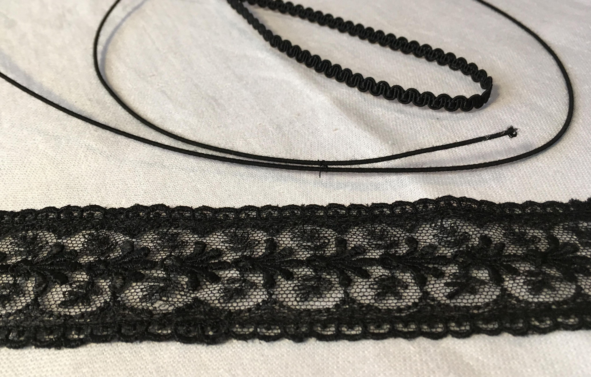 Die Masche entsteht aus schwarzem Hutdraht, auf den eine Spitze und eine Abschlussborte aufgenäht werden.