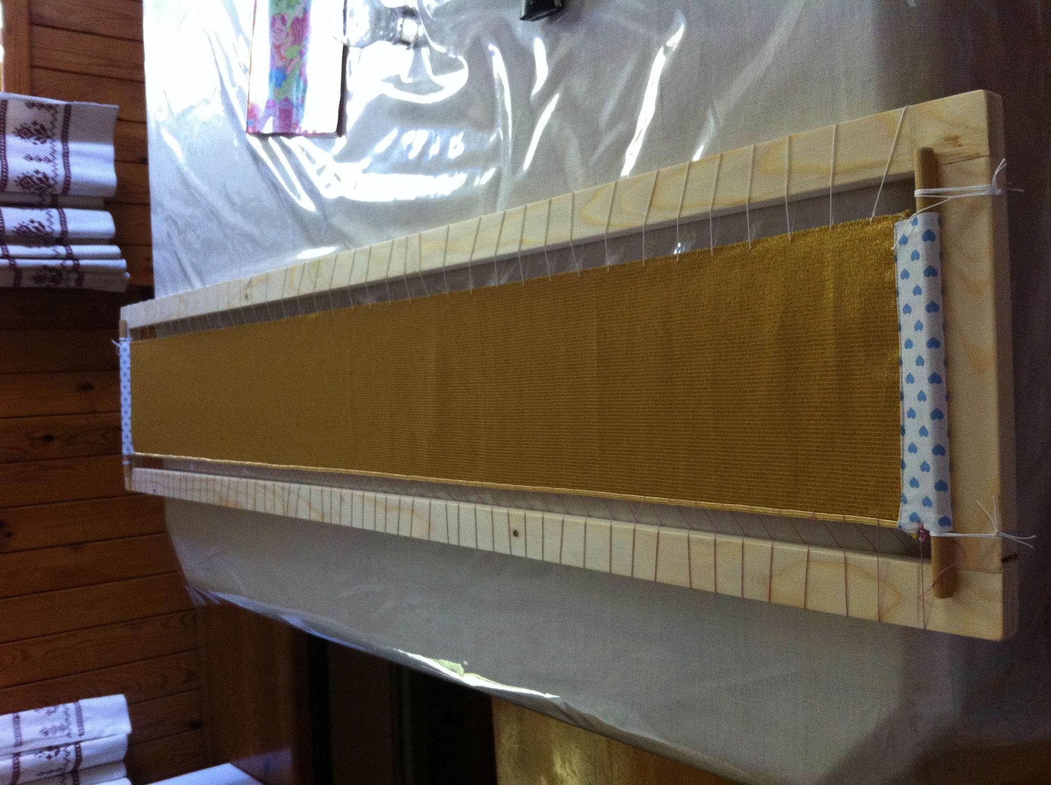Der Goldstoff wird auf einen Rahmen gespannt.