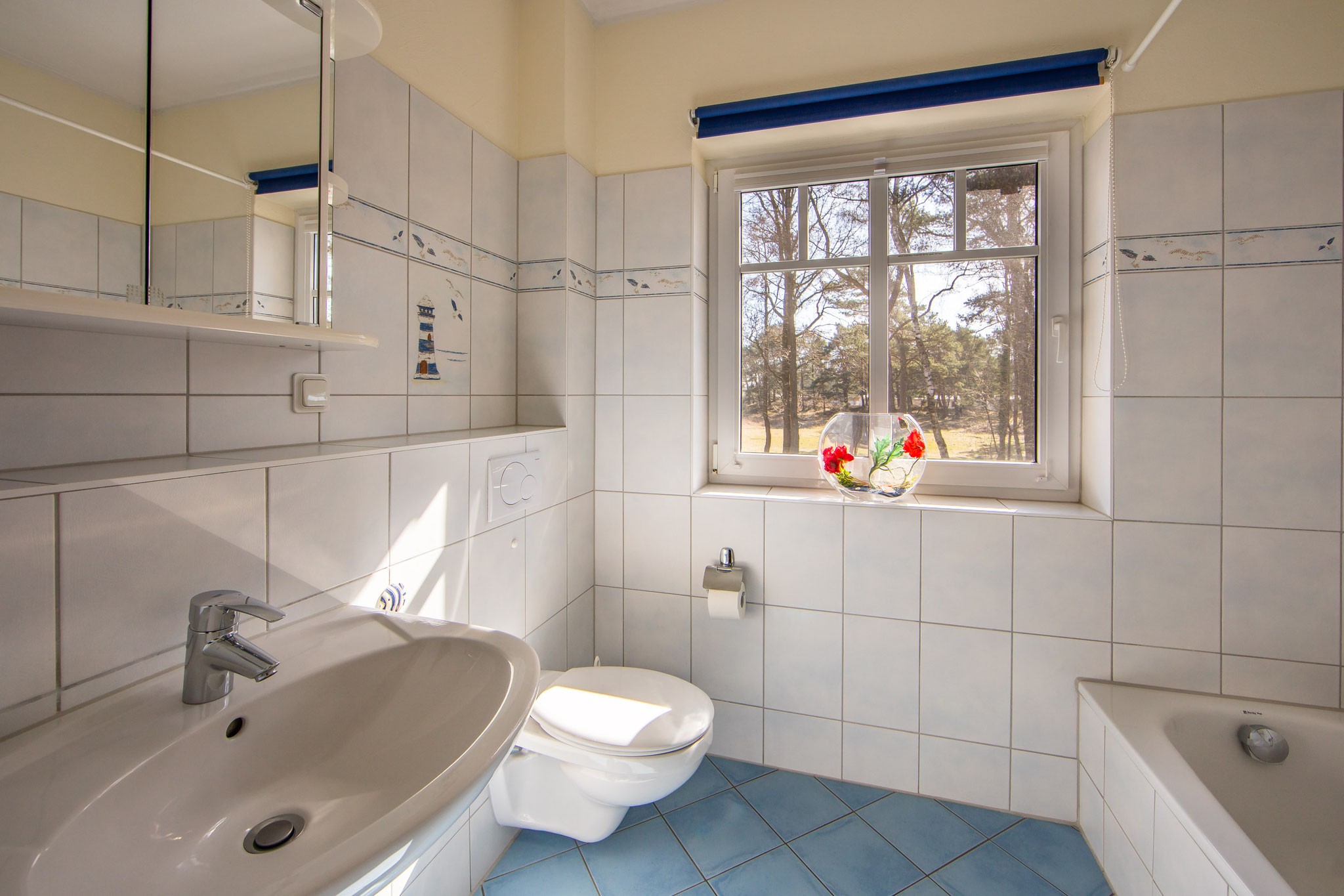 Das Bad im Obergeschoss mit Badewanne, Mückengittern und Verdunkelungsrollos