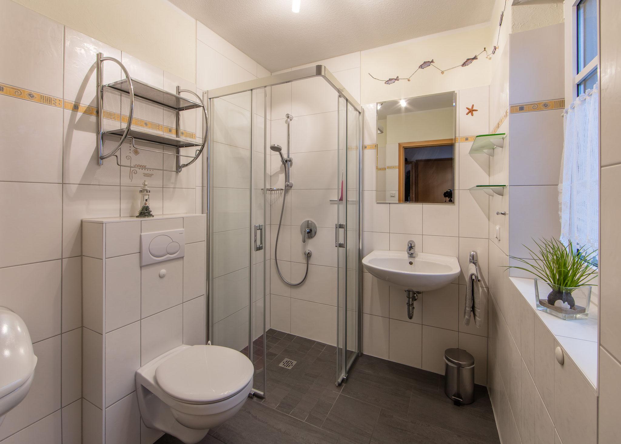 Das untere Badezimmer mit großzügiger Dusche, Urinal und Mückengitter