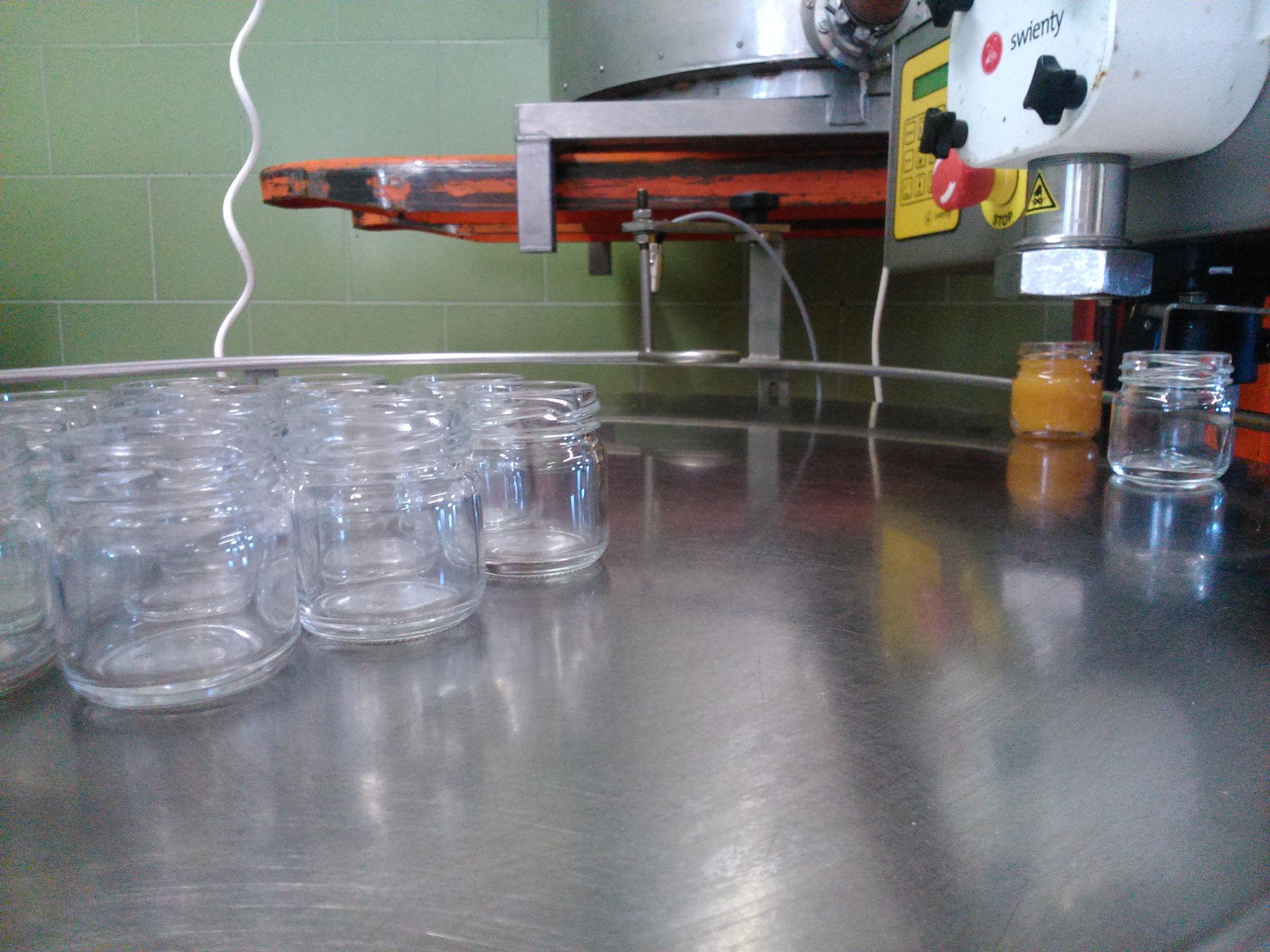 Die Abfüllmaschine in Aktion, der Tisch transportiert die Gläser automatisch weiter...