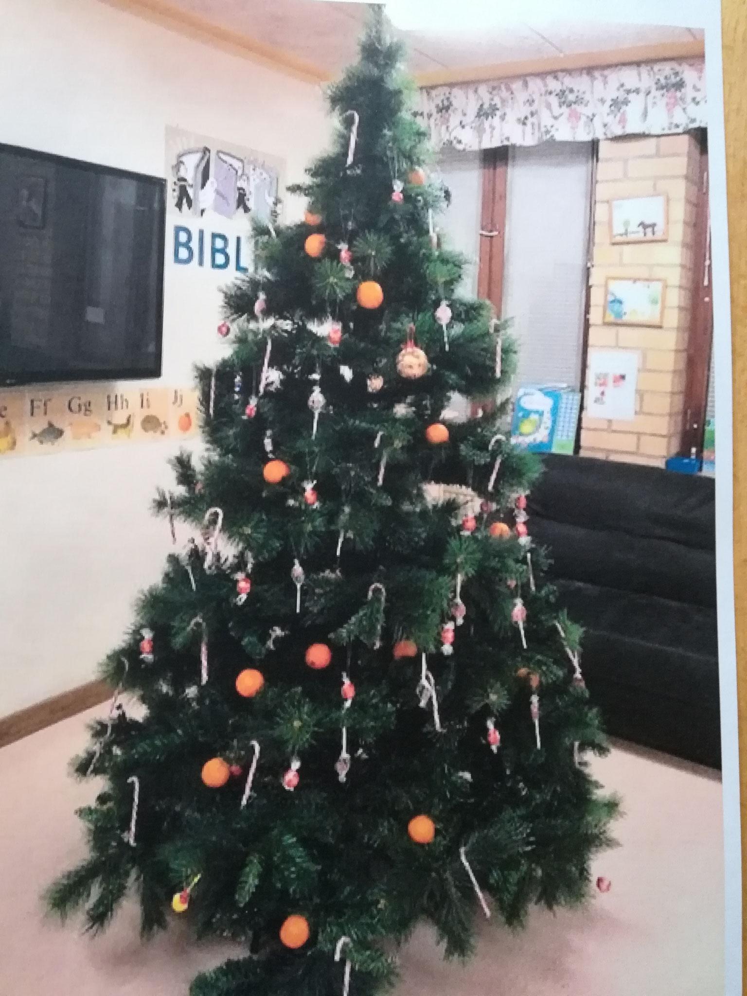 Weihnachtsbaum geschmückt mir Mandarinen und Süßigkeiten