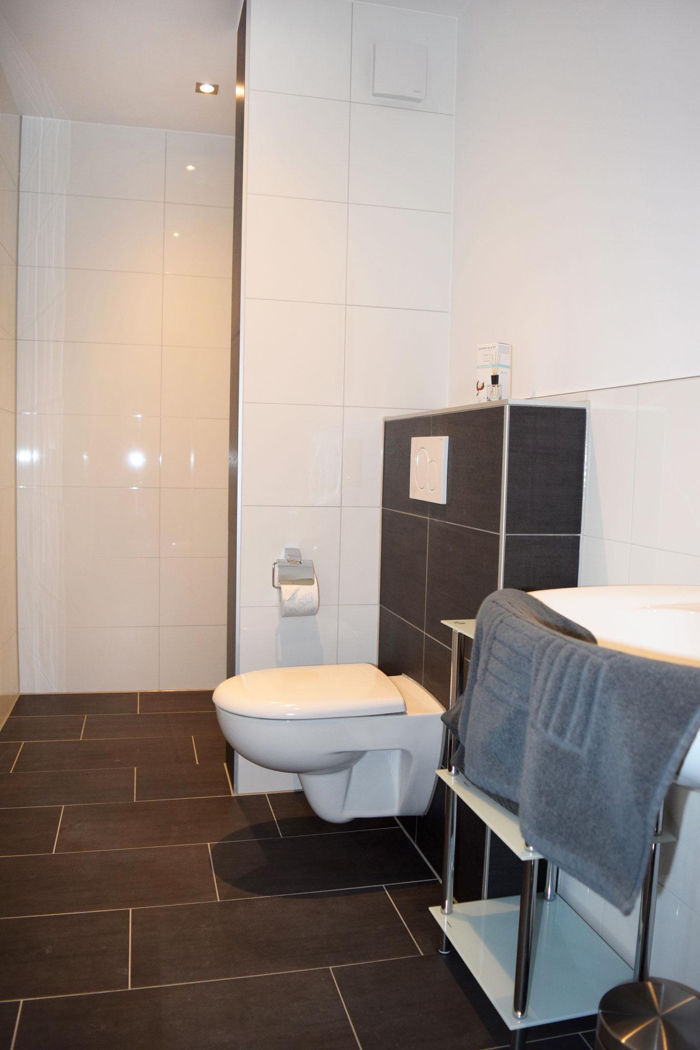 Badezimmer mit bodentiefer Dusche, WC und Waschbecken